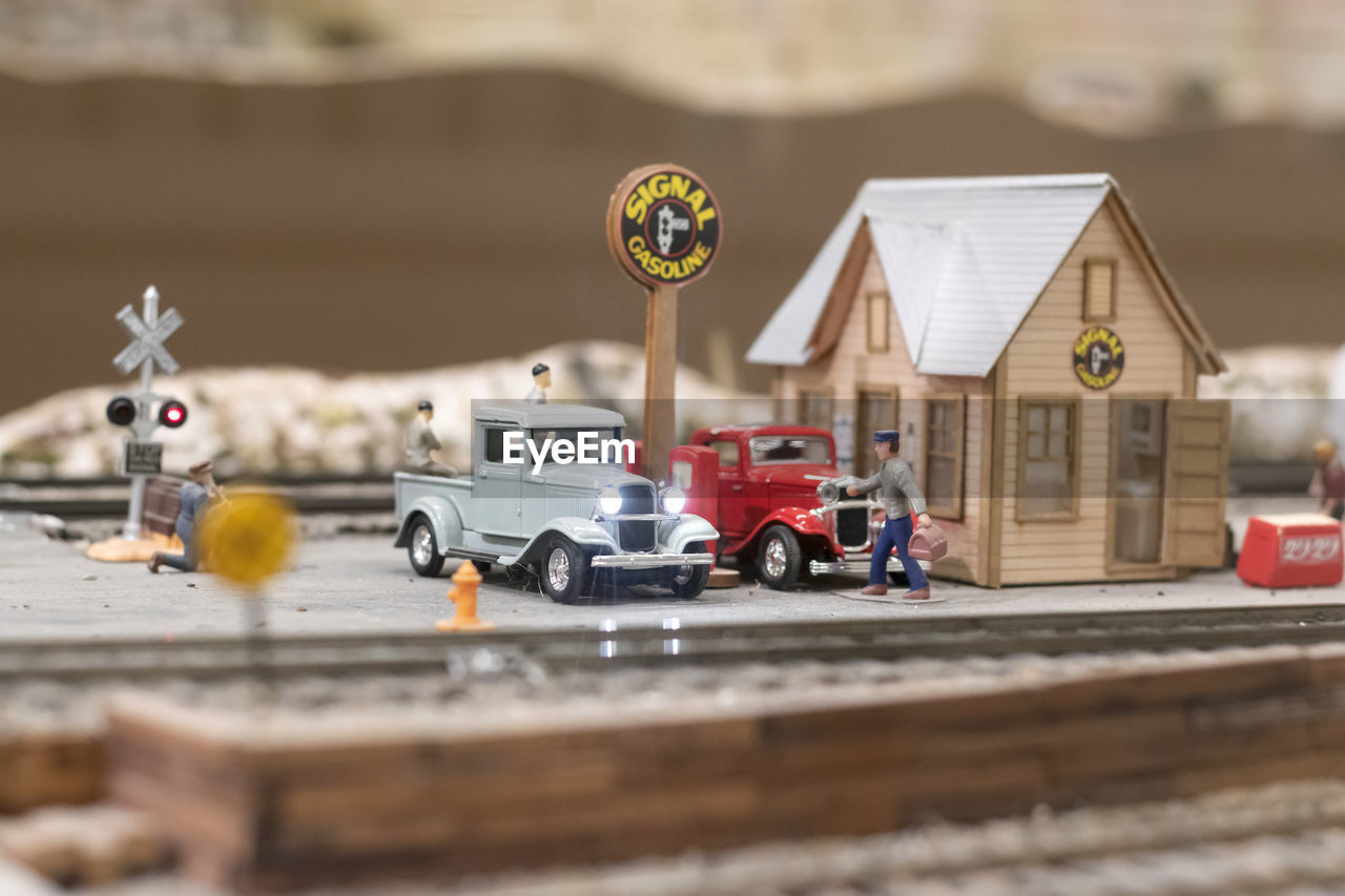 selective focus, transportation, mode of transportation, day, built structure, no people, wood - material, architecture, toy, car, building exterior, motion, representation, land vehicle, outdoors, lighting equipment, close-up, technology, focus on foreground, motor vehicle, small