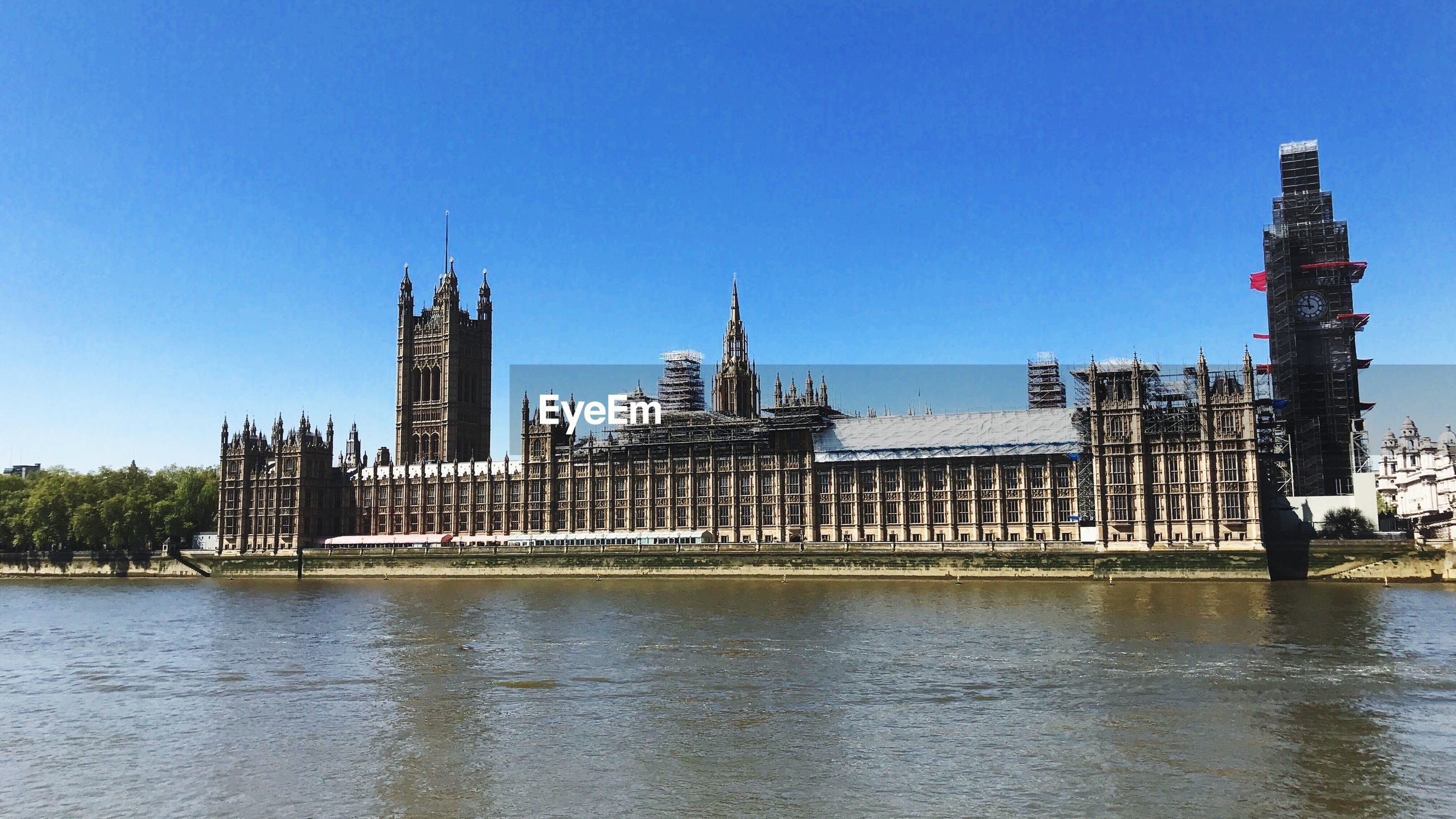 RIVER WITH BUILDINGS IN BACKGROUND AGAINST CLEAR BLUE SKY