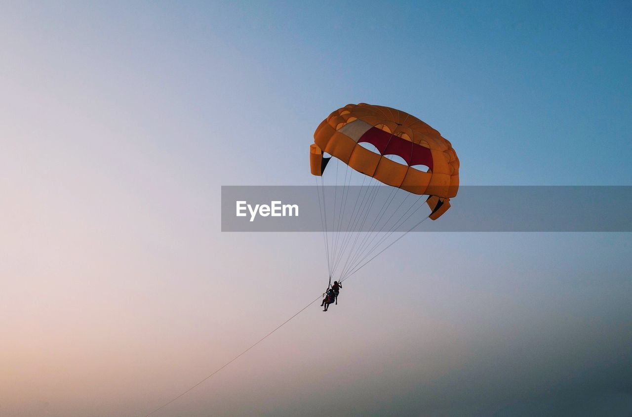 Low Angle View Of Silhouette Friends Parasailing Against Clear Sky During Sunset