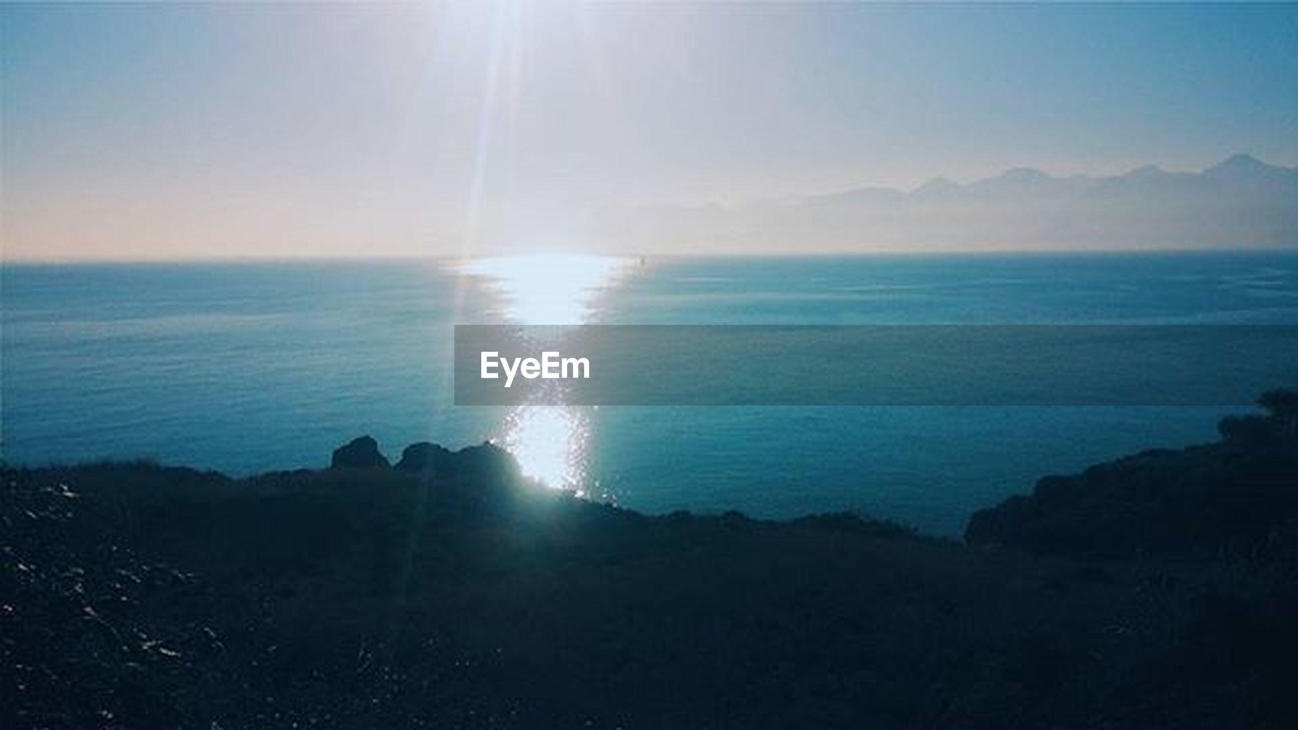 sea, horizon over water, sun, water, tranquil scene, scenics, tranquility, beauty in nature, sunbeam, sunlight, lens flare, sky, nature, idyllic, blue, reflection, beach, sunny, shore, clear sky