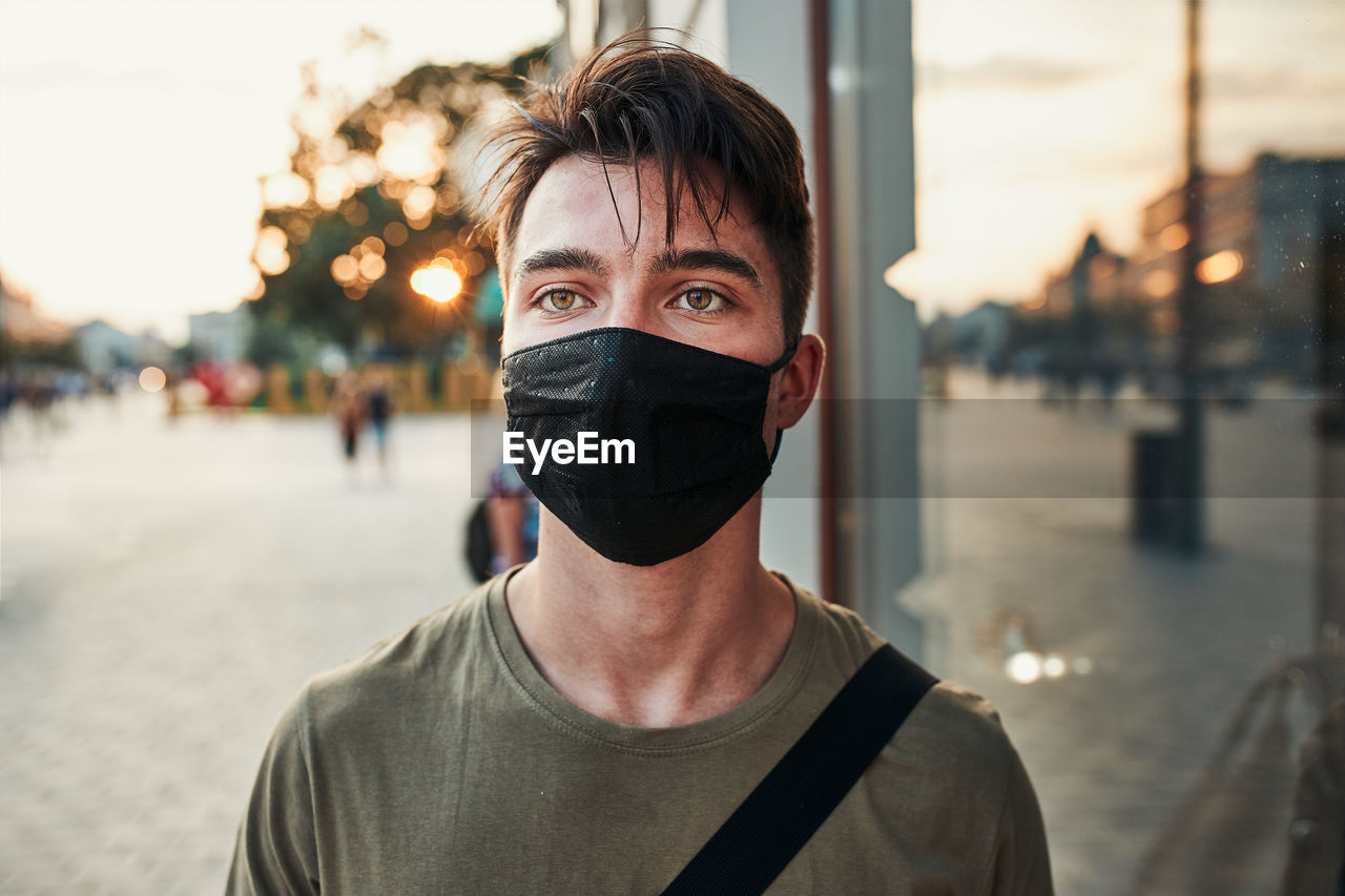 Portrait of young man wearing mask standing in city