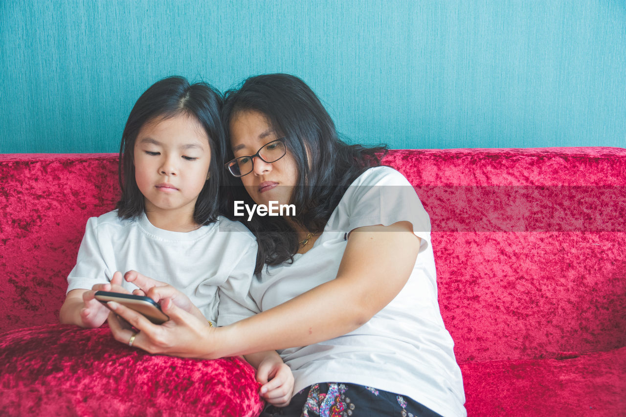 wireless technology, technology, mobile phone, togetherness, connection, smart phone, bonding, portable information device, women, females, childhood, casual clothing, real people, girls, child, leisure activity, lifestyles, furniture, communication, black hair, hair, positive emotion