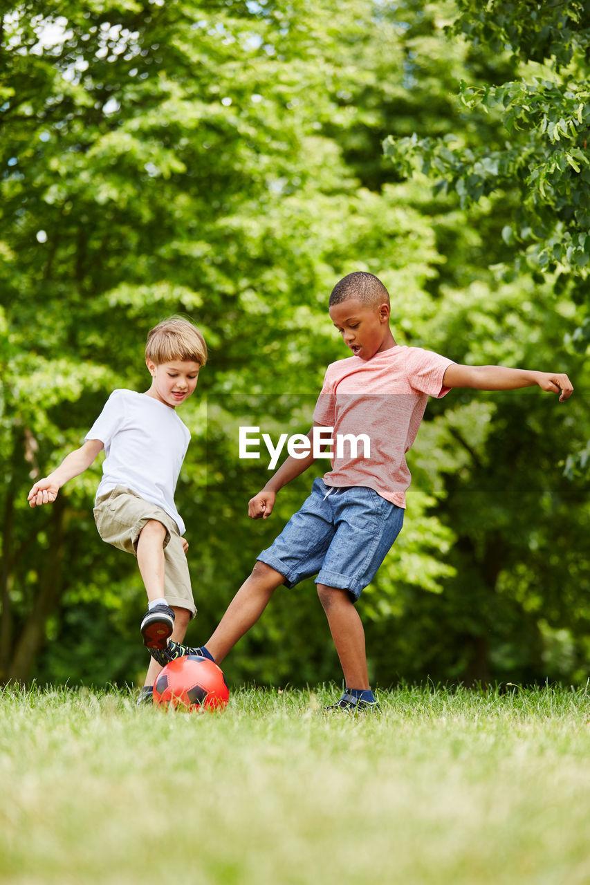 Full Length Of Boys Playing Soccer On Grassy Field
