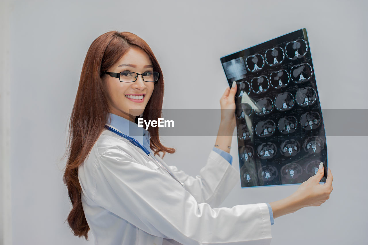 healthcare and medicine, doctor, young adult, expertise, indoors, occupation, adult, glasses, one person, waist up, medical exam, portrait, eyeglasses, professional occupation, clothing, technology, young women, hospital, medical x-ray, lab coat, mri scan, hairstyle, analyzing