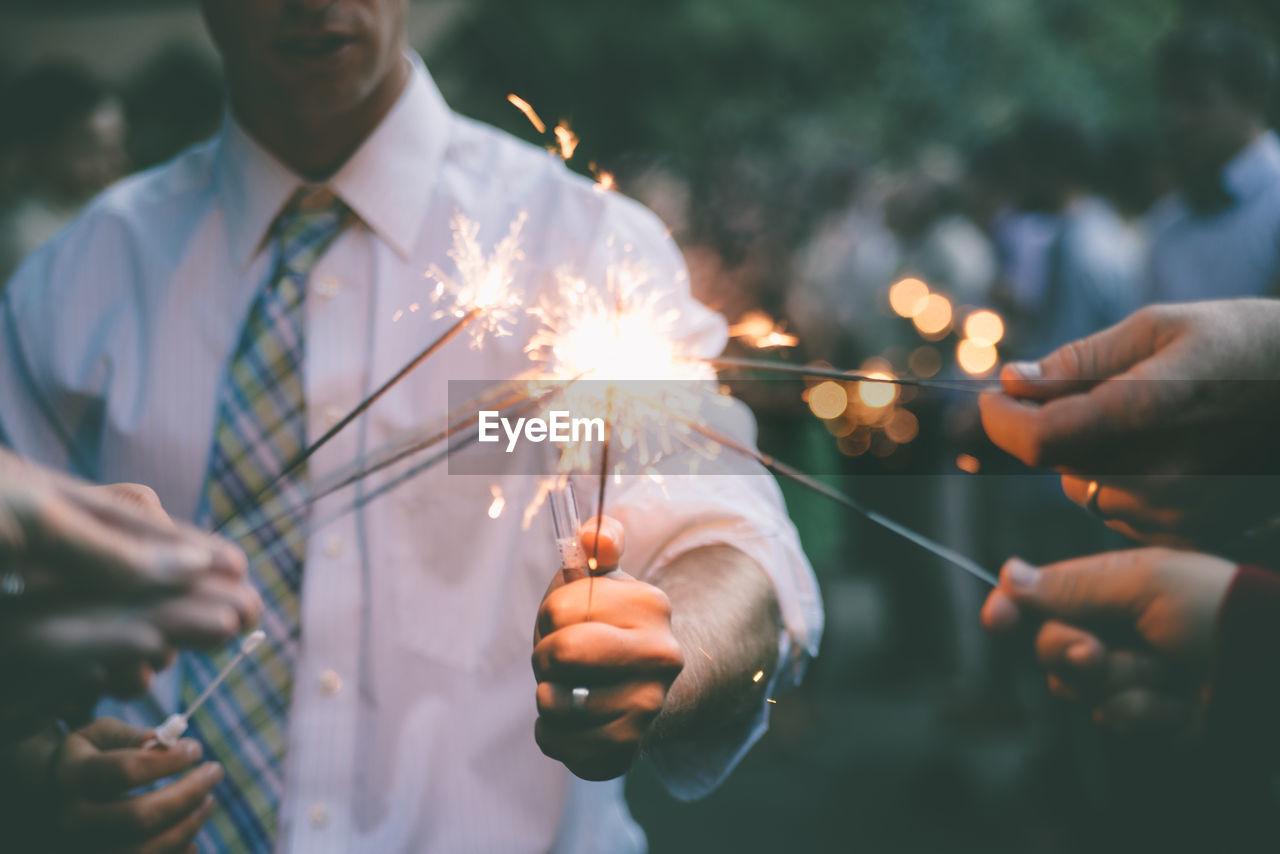 Close-Up Of Friends Igniting Sparklers At Party