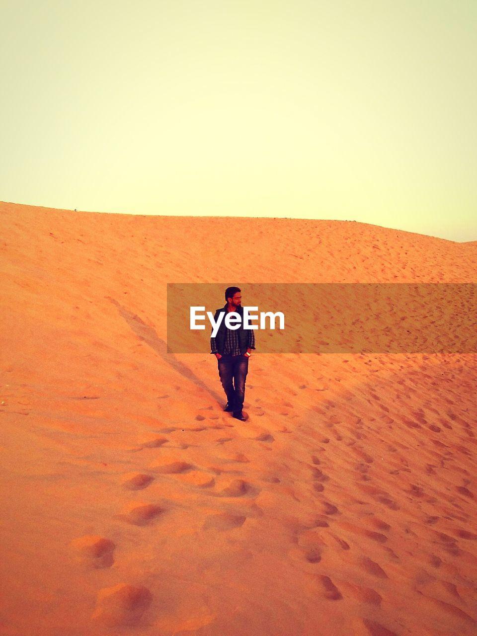 Full length of man standing at desert against sky