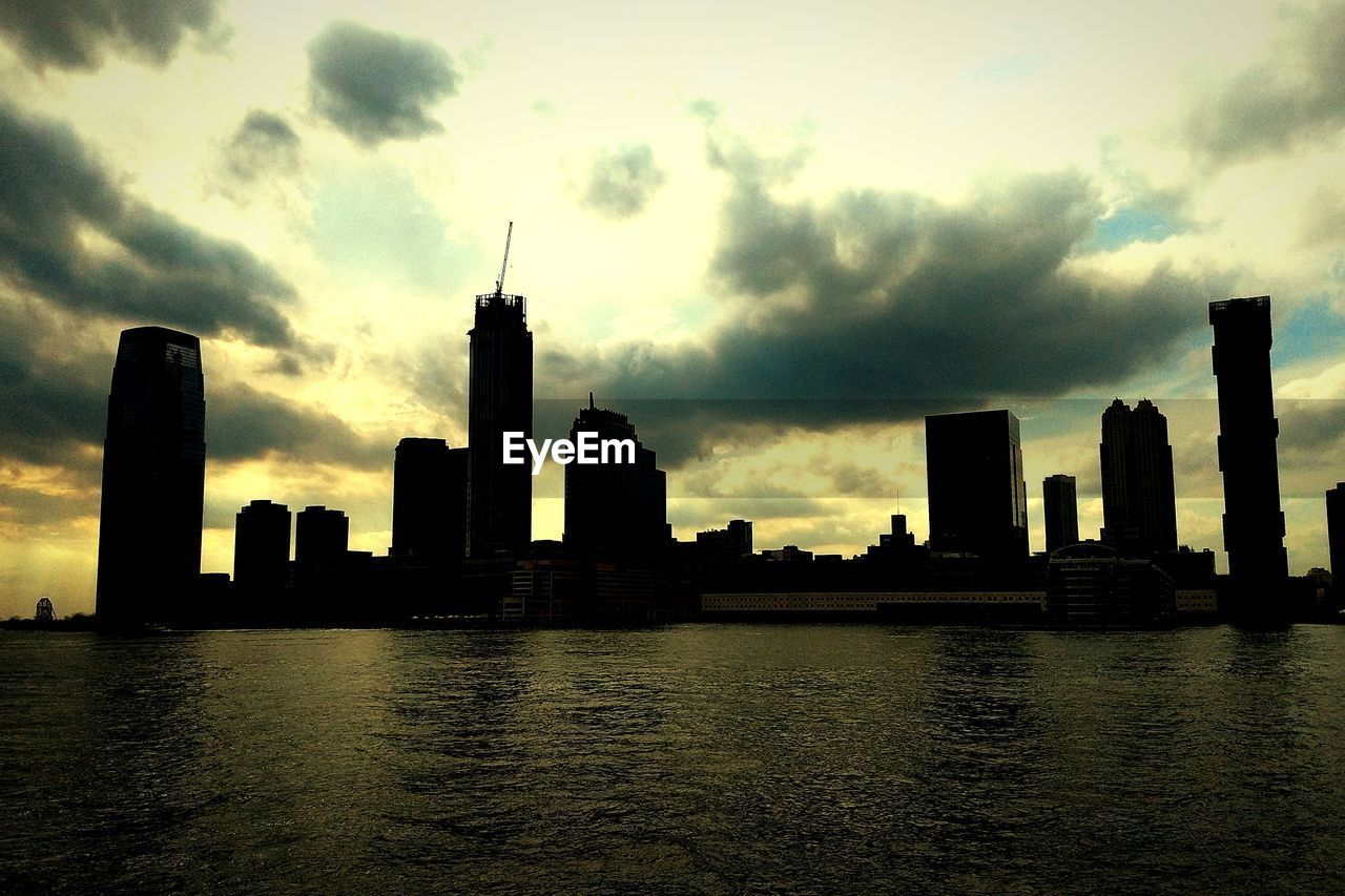 sky, building exterior, built structure, architecture, cloud - sky, city, water, building, office building exterior, skyscraper, sunset, waterfront, tall - high, urban skyline, tower, river, no people, landscape, silhouette, cityscape, modern, outdoors, spire, financial district