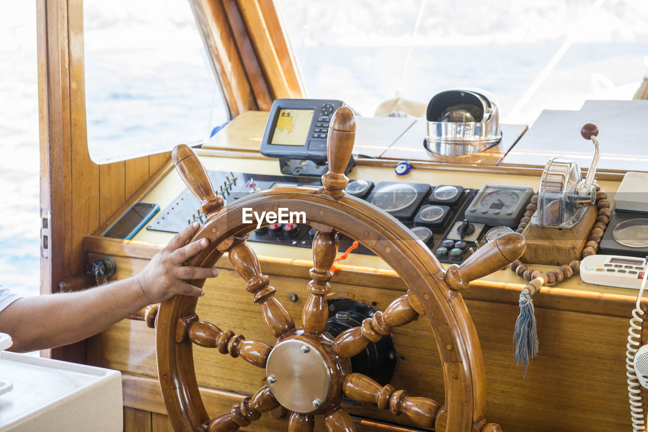 steering wheel, human hand, one person, transportation, control, real people, mode of transportation, hand, human body part, nautical vessel, vehicle interior, wood - material, holding, helm, unrecognizable person, indoors, control panel, men, day, wheel, finger, sailboat