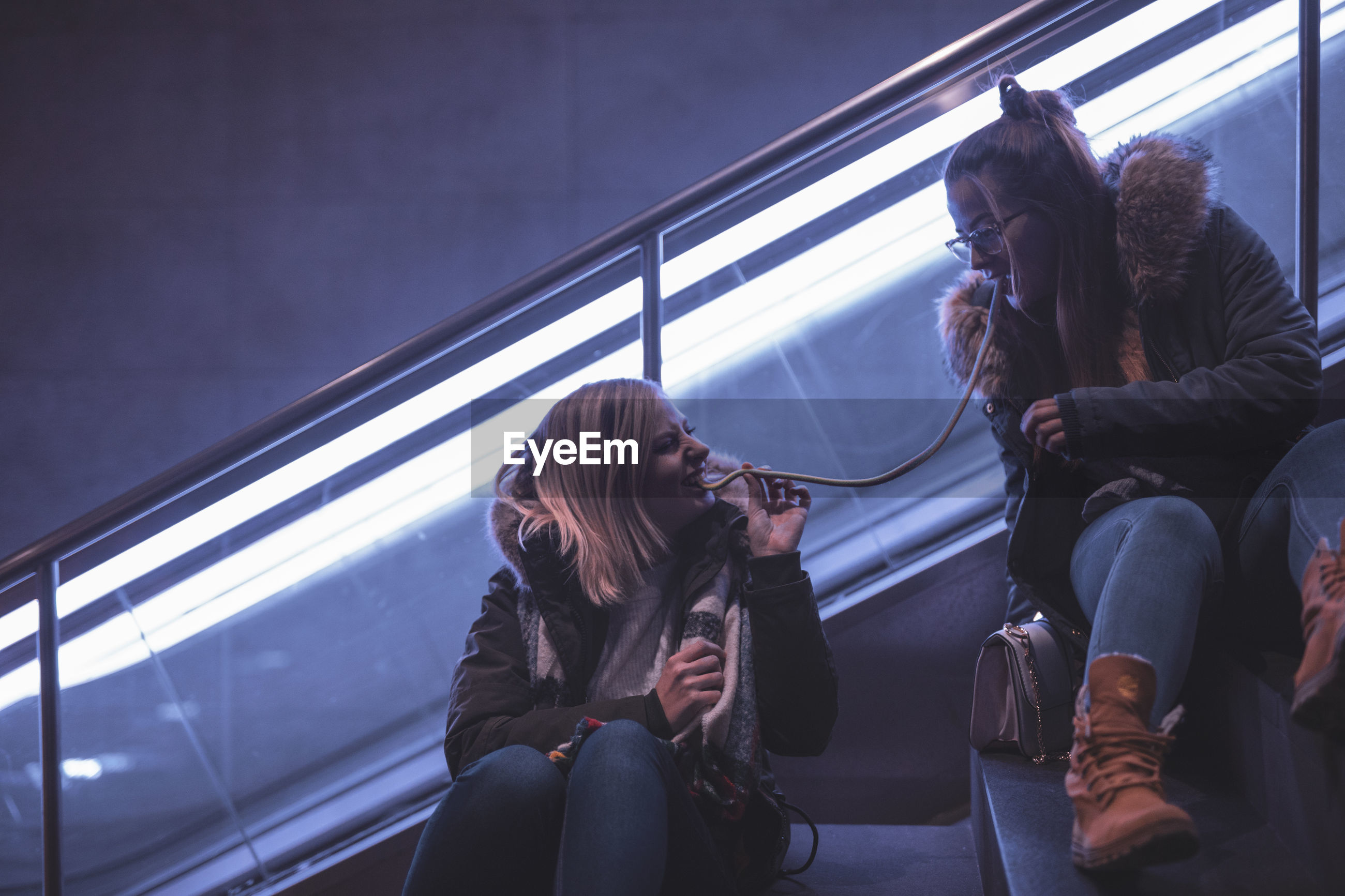 Female friends eating food while sitting on escalator