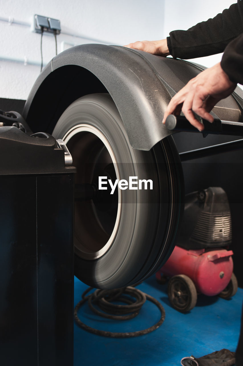 Cropped hands of mechanic with tire in machine at auto repair shop