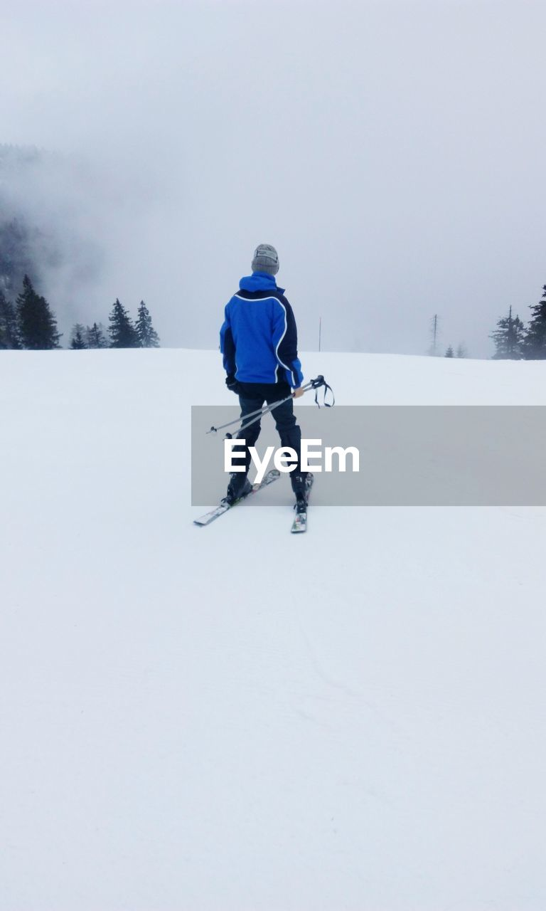Rear View Of Man Skiing On Snow Covered Mountains