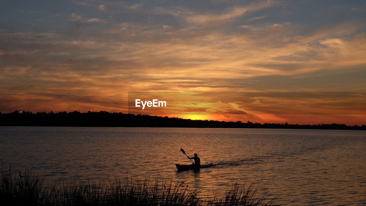 sunset, sky, water, cloud - sky, beauty in nature, scenics - nature, silhouette, orange color, nautical vessel, waterfront, tranquil scene, transportation, tranquility, mode of transportation, real people, nature, lake, one person, idyllic, rowing, outdoors