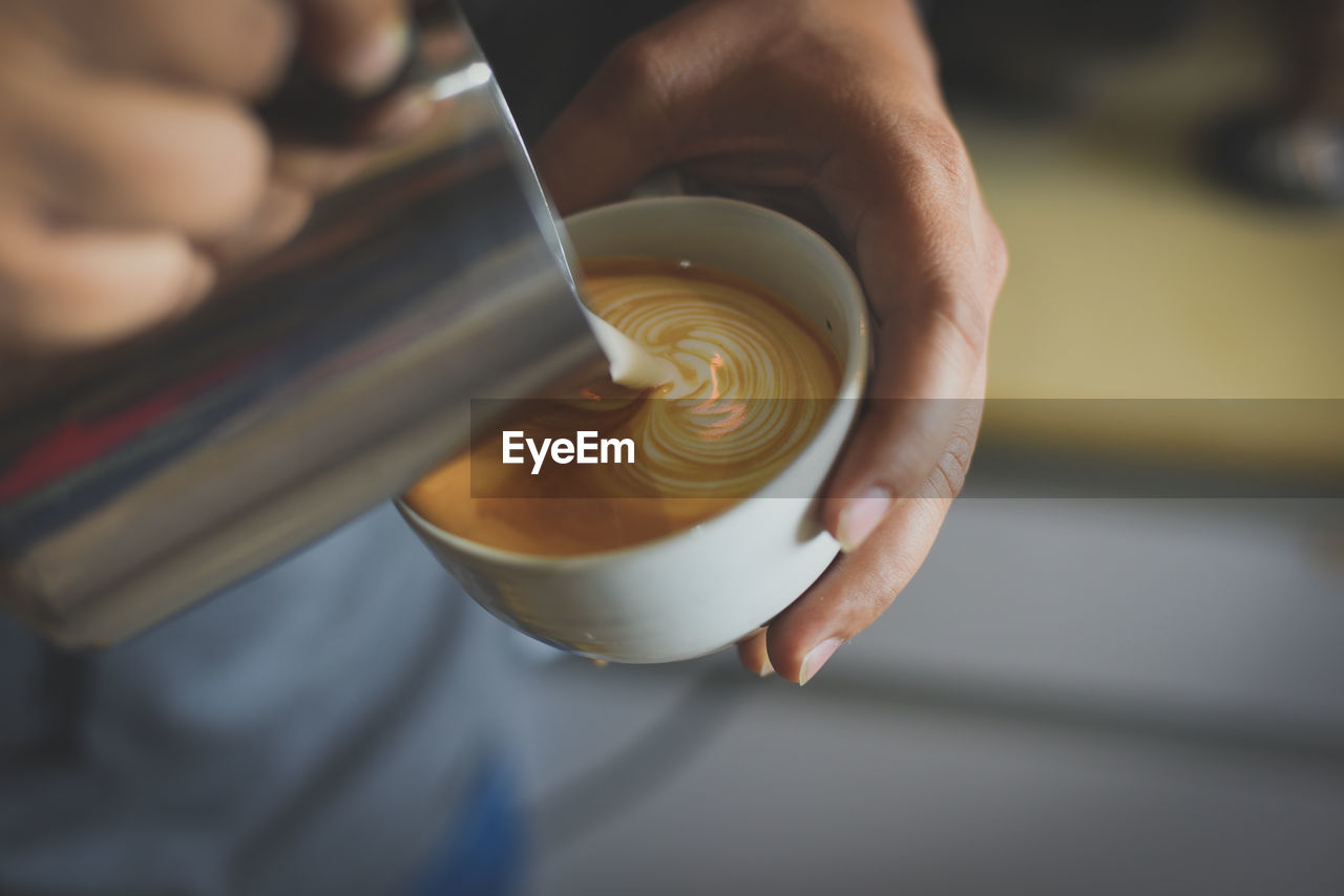 food and drink, cup, human hand, coffee, mug, one person, hand, real people, coffee cup, coffee - drink, drink, hot drink, cappuccino, refreshment, holding, indoors, focus on foreground, froth art, human body part, working, preparation, barista, frothy drink, latte, finger, coffee shop