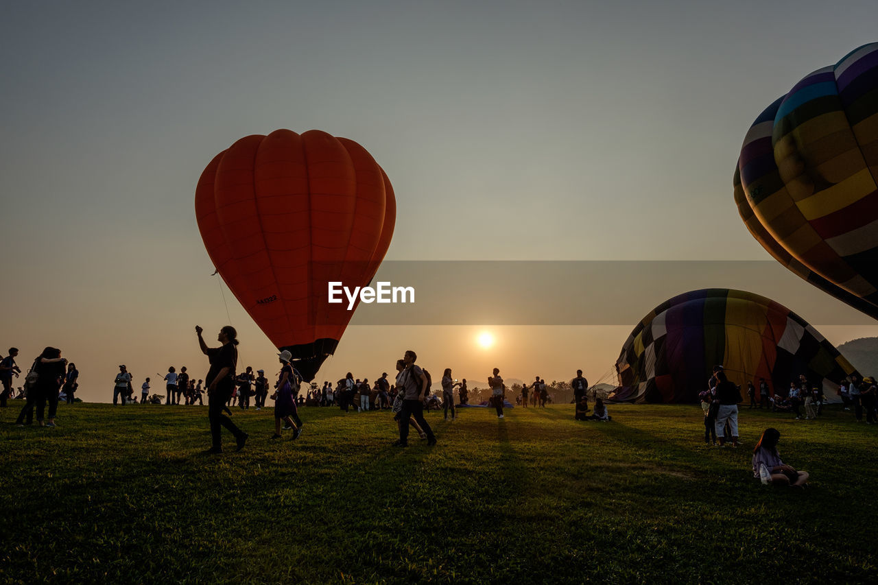 group of people, crowd, large group of people, sky, real people, sunset, men, nature, air vehicle, leisure activity, balloon, field, grass, land, hot air balloon, lifestyles, women, outdoors, flying, lens flare, ballooning festival
