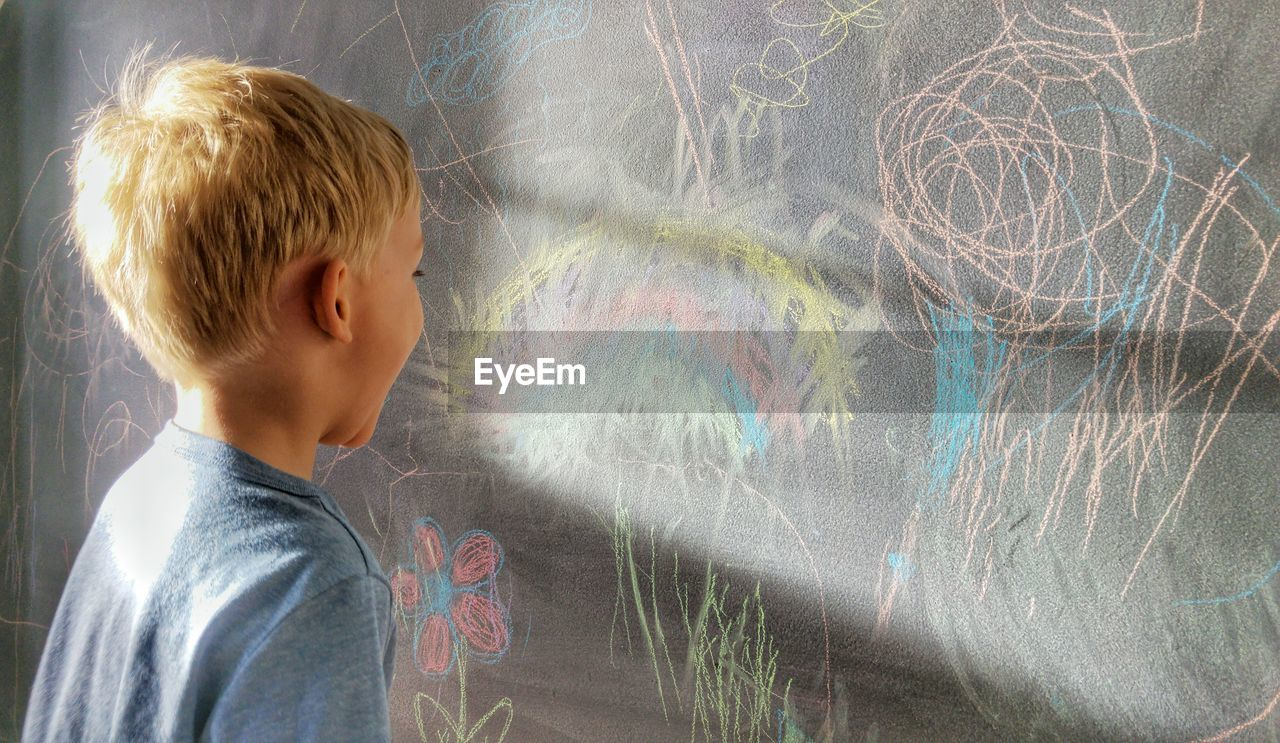 Close-up of child laughing in front of scribbles on chalkboard