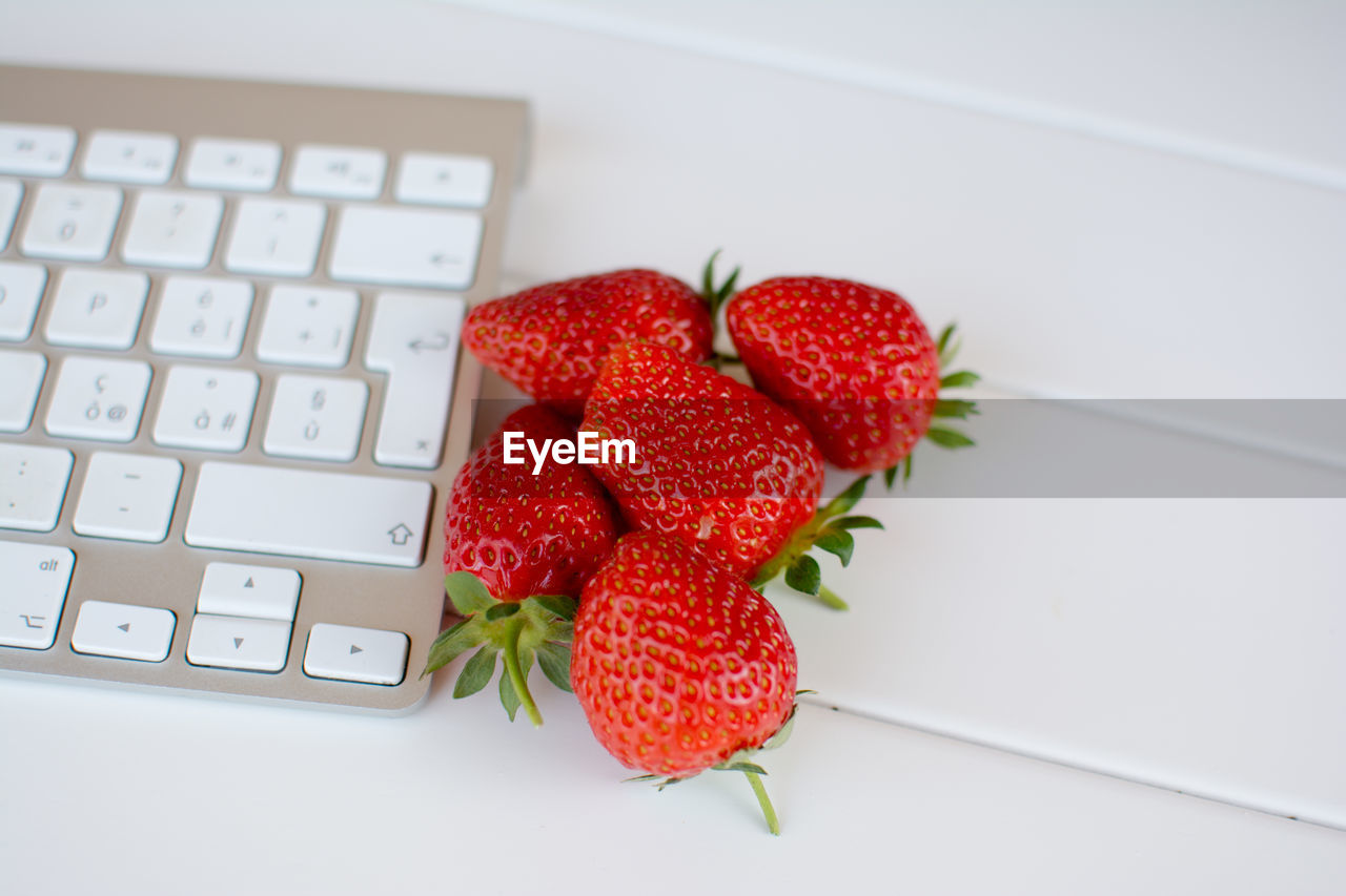 Computer Keyboard And Strawberries On Table