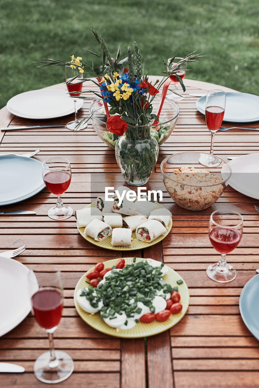 Dinner in an apple orchard garden on wooden table with salads and wine decorated with flowers