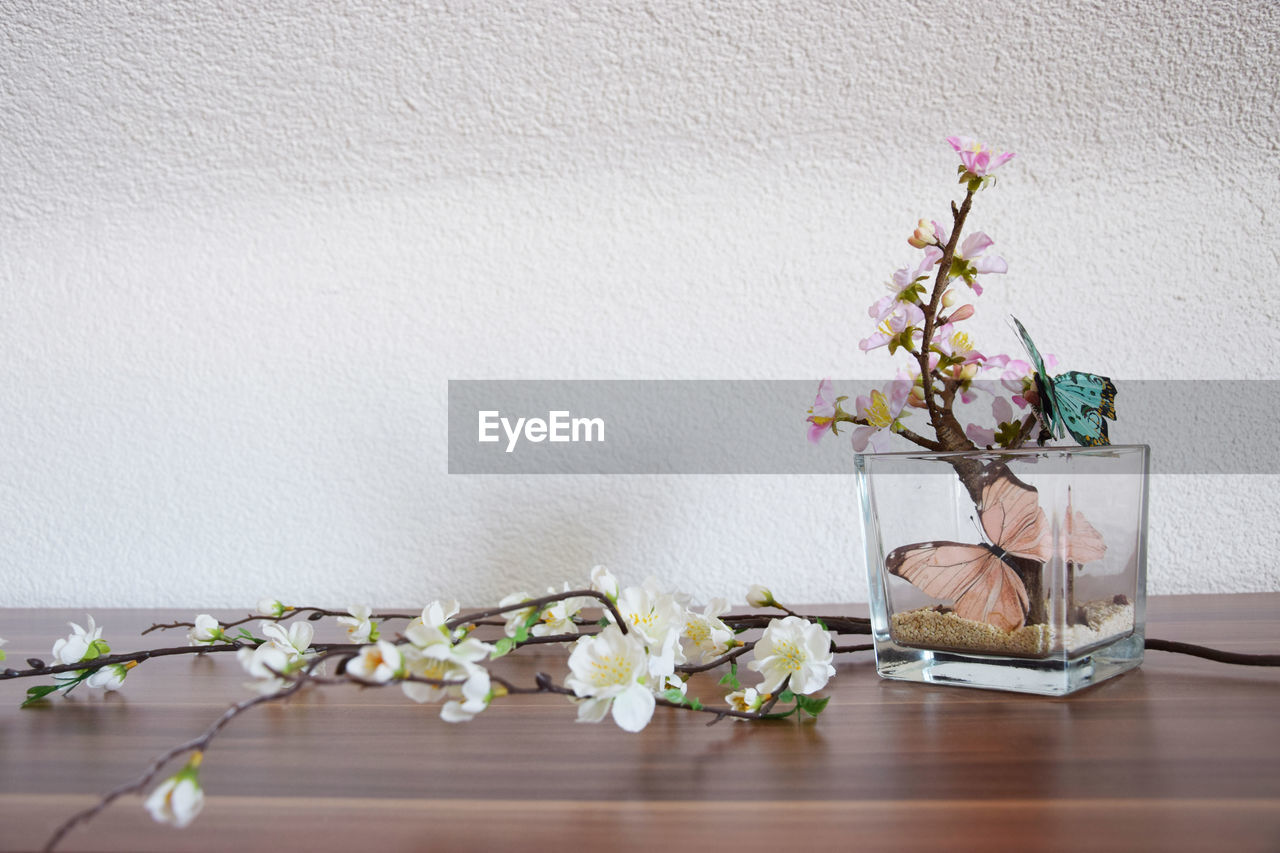 Close-up of ikebana with artificial butterflies on table against white wall