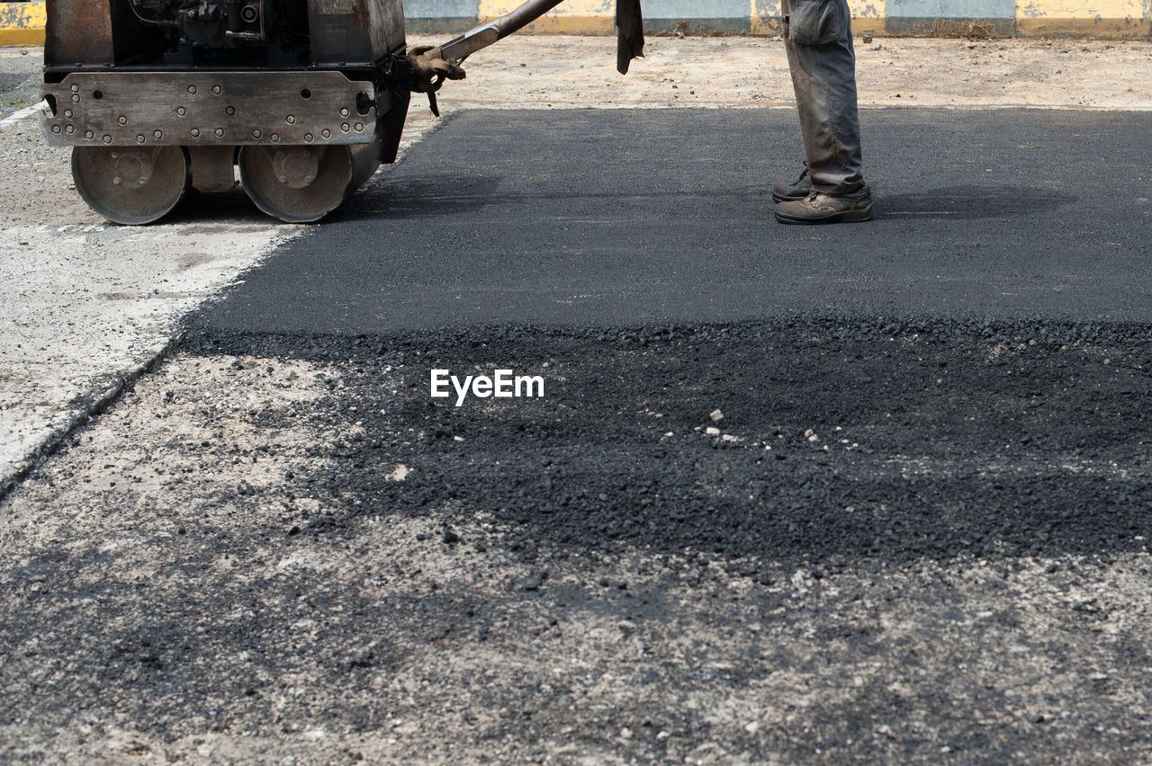 Low section of man pouring hot asphalt