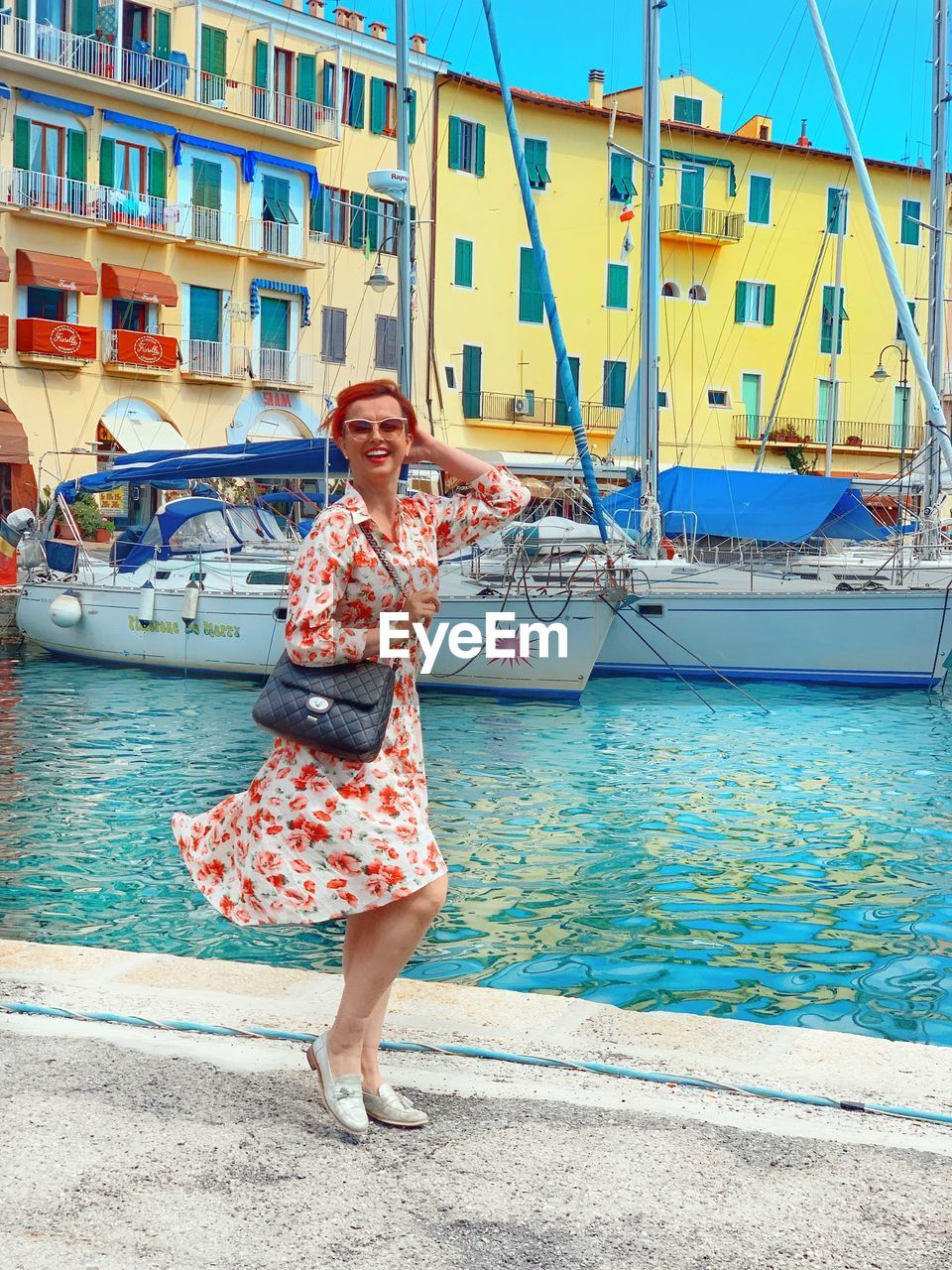 nautical vessel, transportation, water, one person, leisure activity, real people, mode of transportation, full length, portrait, lifestyles, young adult, looking at camera, women, sea, smiling, casual clothing, young women, fashion, harbor, outdoors, beautiful woman