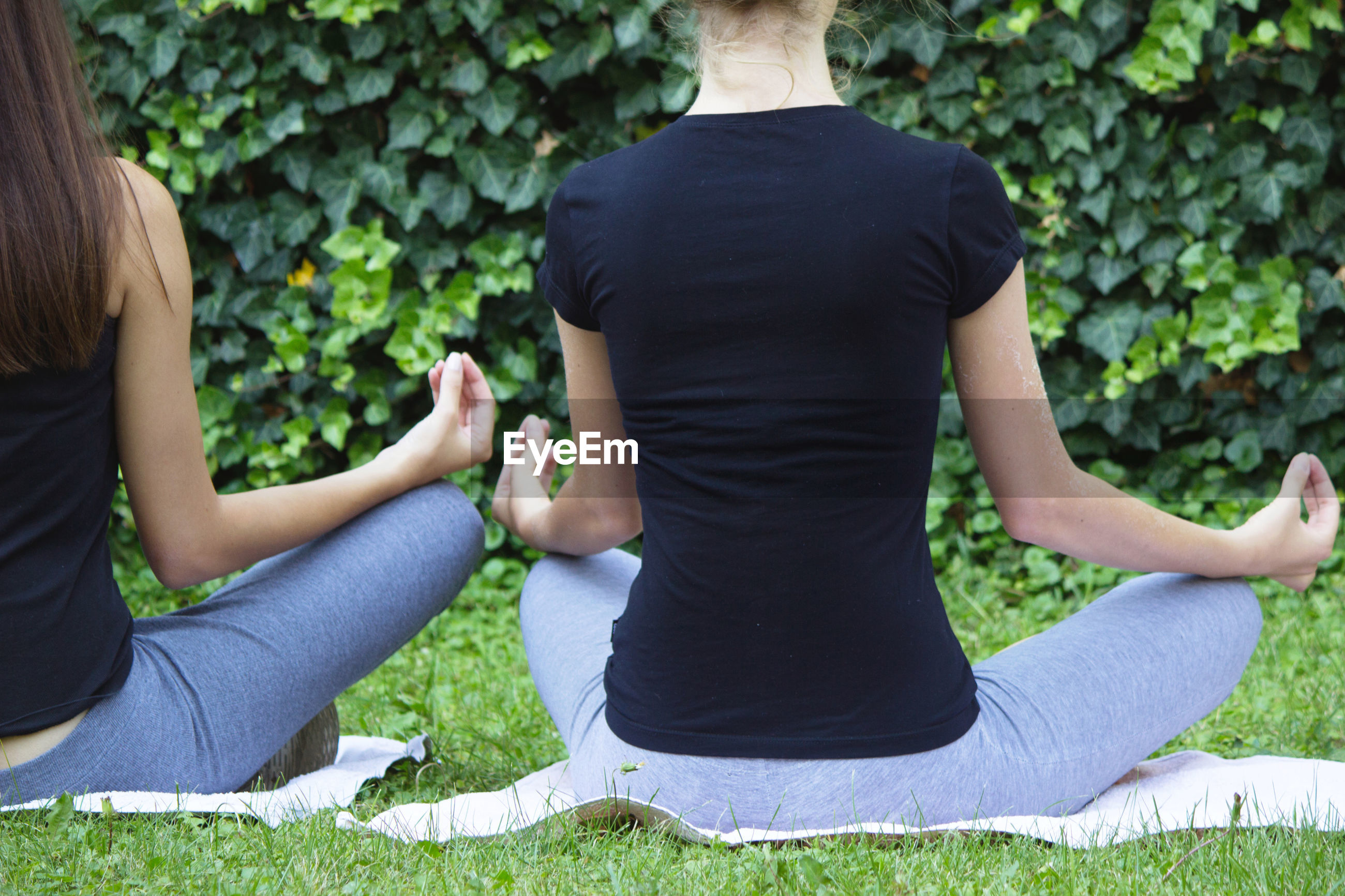 MIDSECTION OF WOMAN SITTING ON GRASS