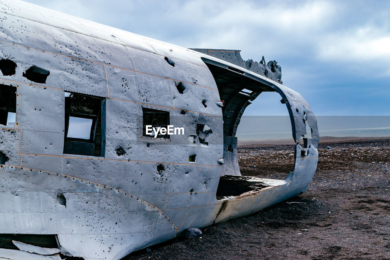 Crashed Airplane On Barren Field Against Sky