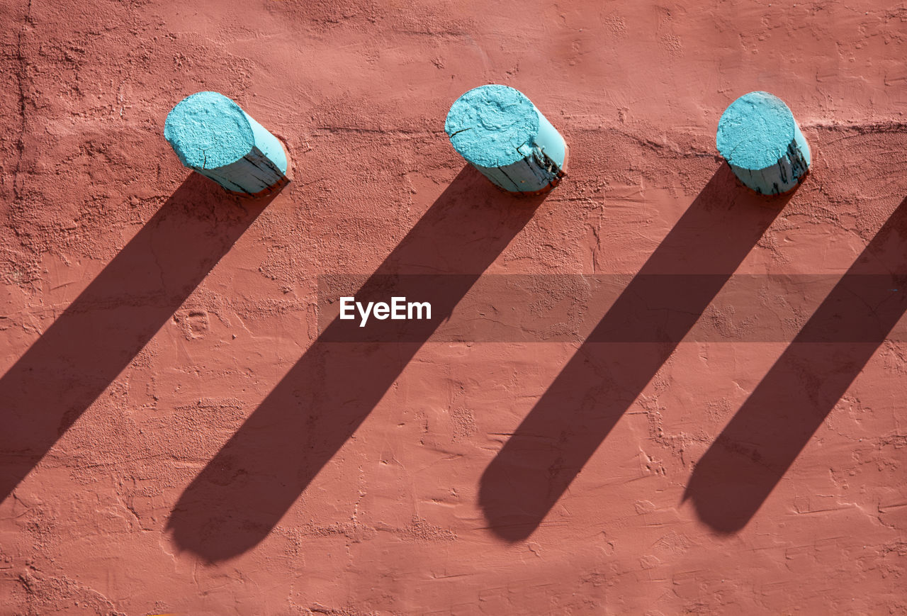 no people, wall - building feature, shadow, high angle view, sunlight, day, built structure, side by side, sweet food, architecture, outdoors, still life, blue, nature, full frame, art and craft, group of objects, close-up, creativity, indulgence, turquoise colored