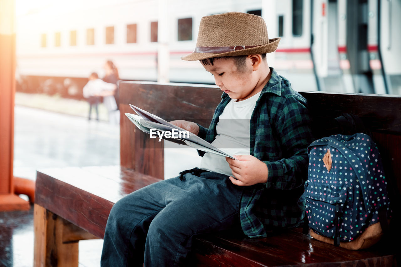 hat, sitting, real people, clothing, young adult, lifestyles, three quarter length, one person, leisure activity, young men, connection, casual clothing, holding, focus on foreground, communication, technology, wireless technology, men, outdoors