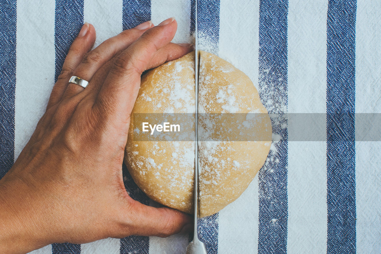 Cropped image of hand cutting bread on table at home