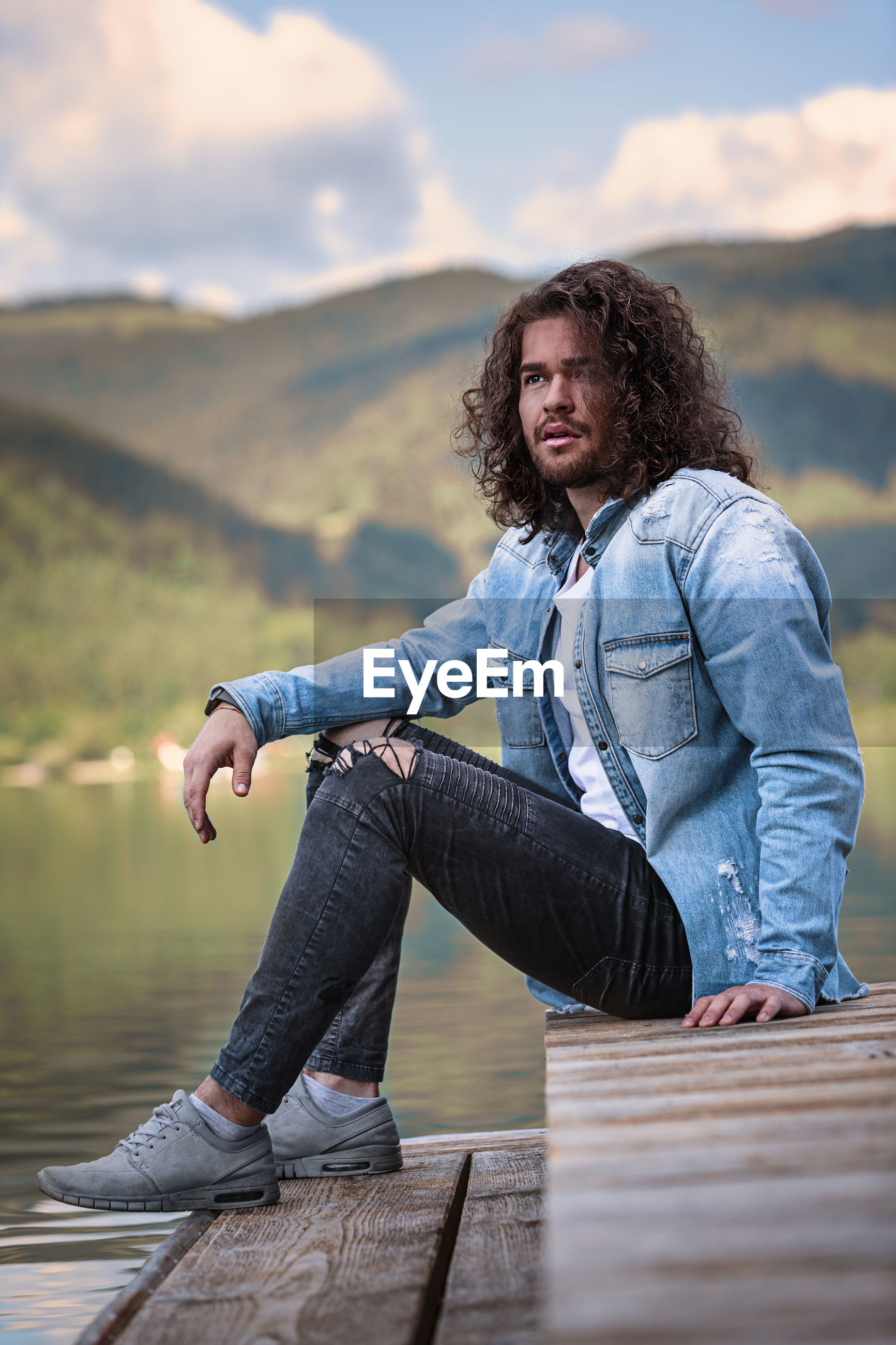 Young man looking away while sitting at lake