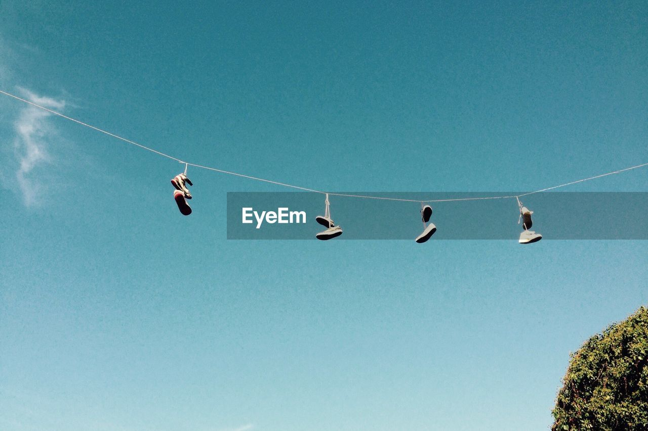 Low Angle View Of Shoe Pairs Hanging On Rope Against Sky