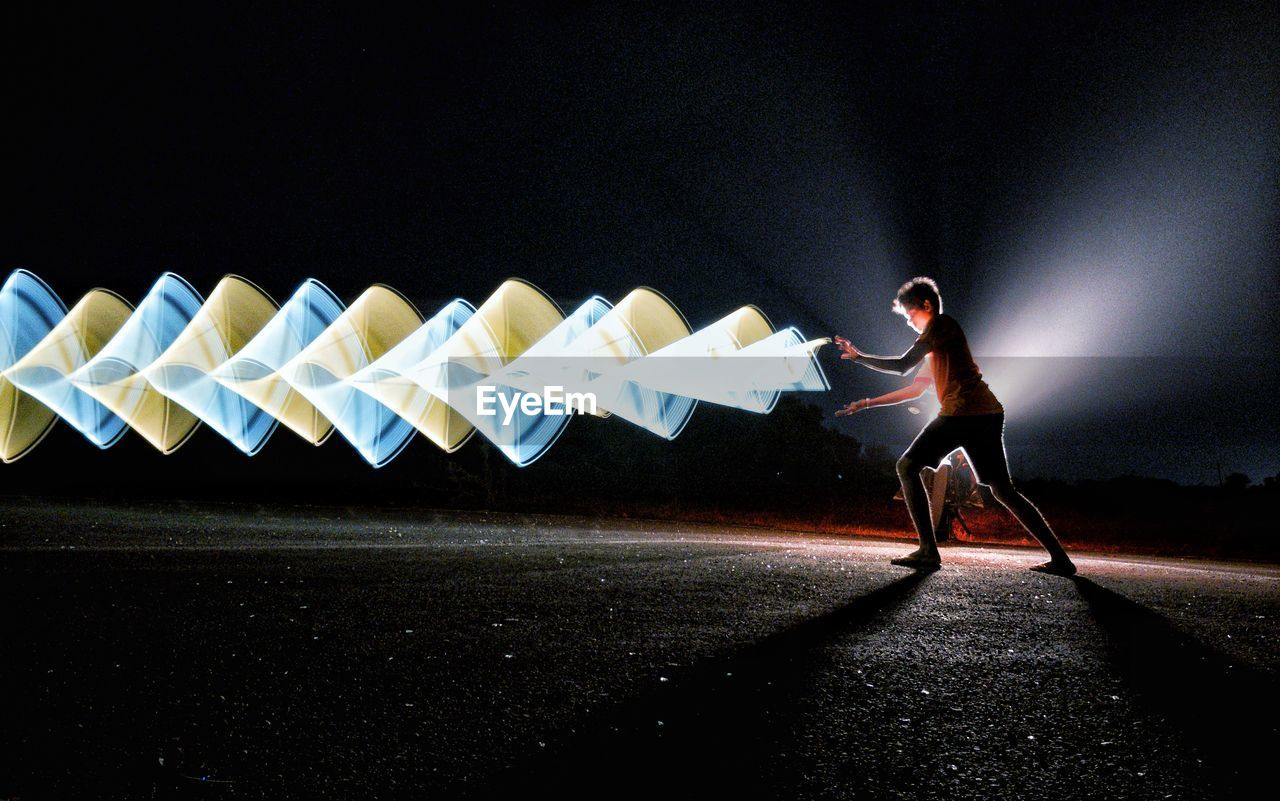 Side View Of Man By Light Painting On Road At Night