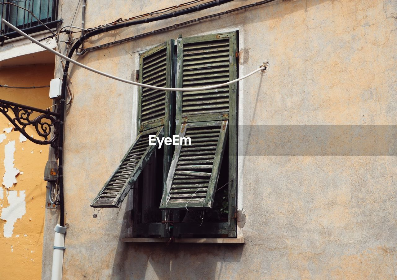 built structure, architecture, building exterior, window, building, wall - building feature, no people, residential district, day, low angle view, old, house, wall, outdoors, shutter, weathered, metal, damaged, close-up, closed