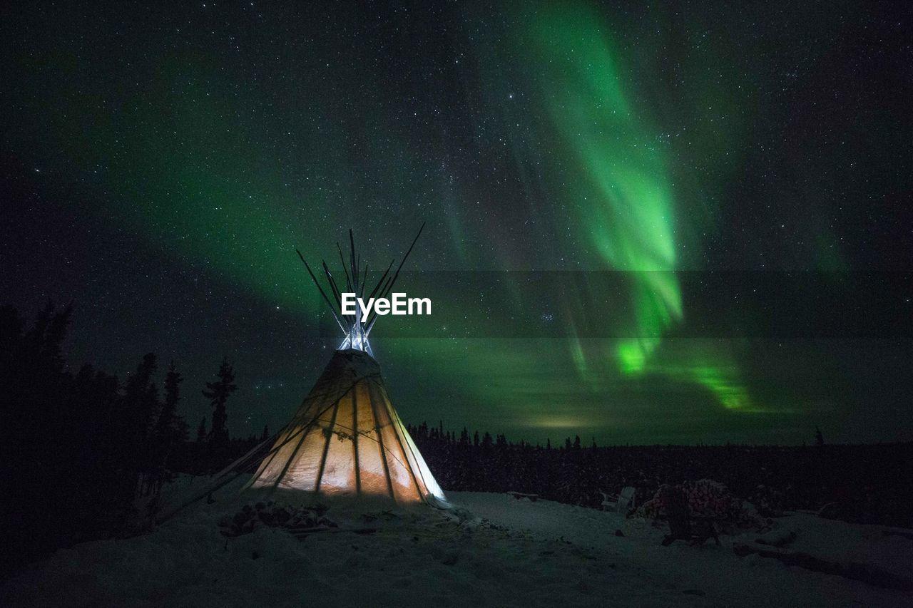 Illuminated Tent Against Aurora Borealis In Sky At Night