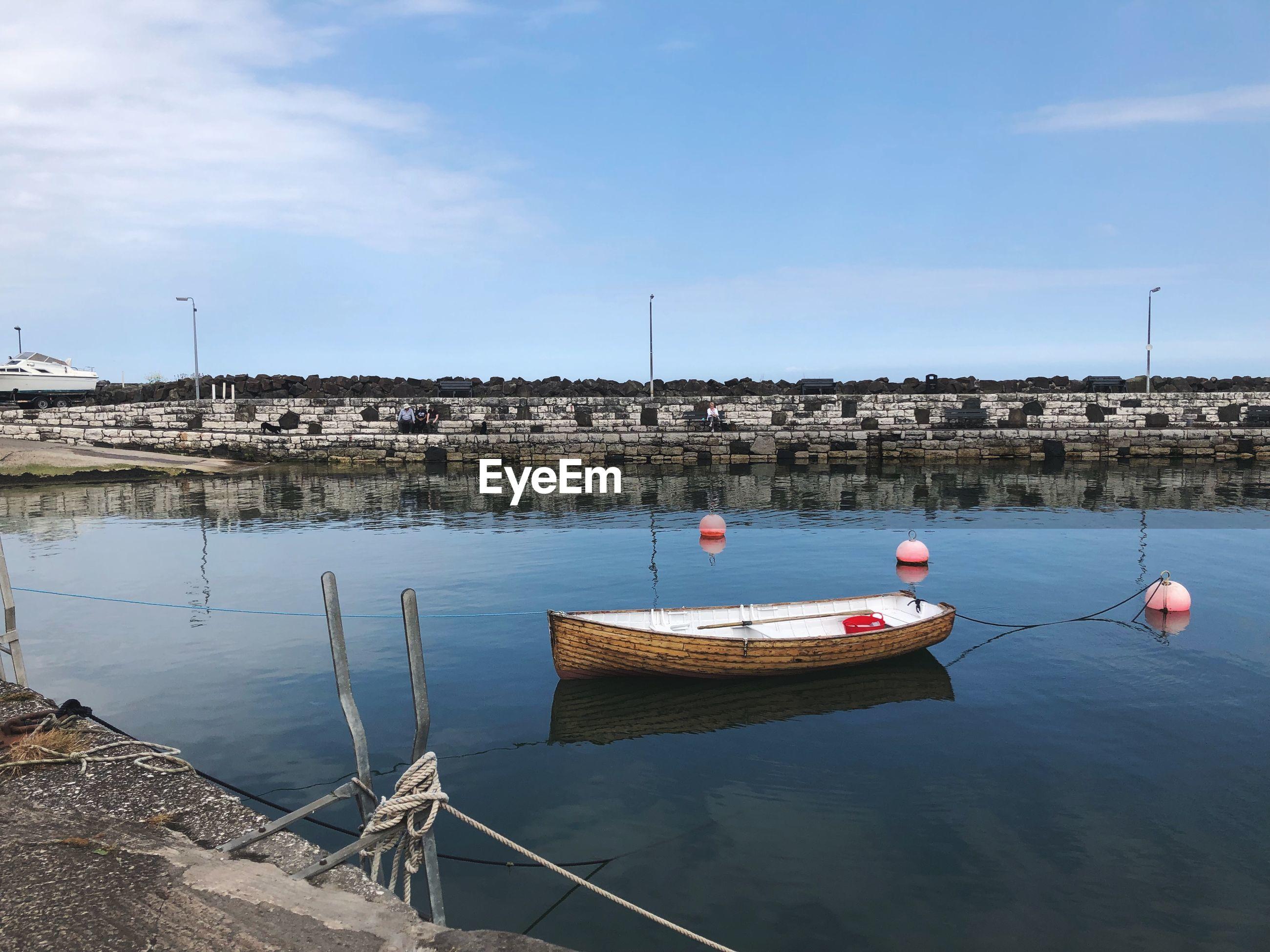 Rowboat moored in lake against sky