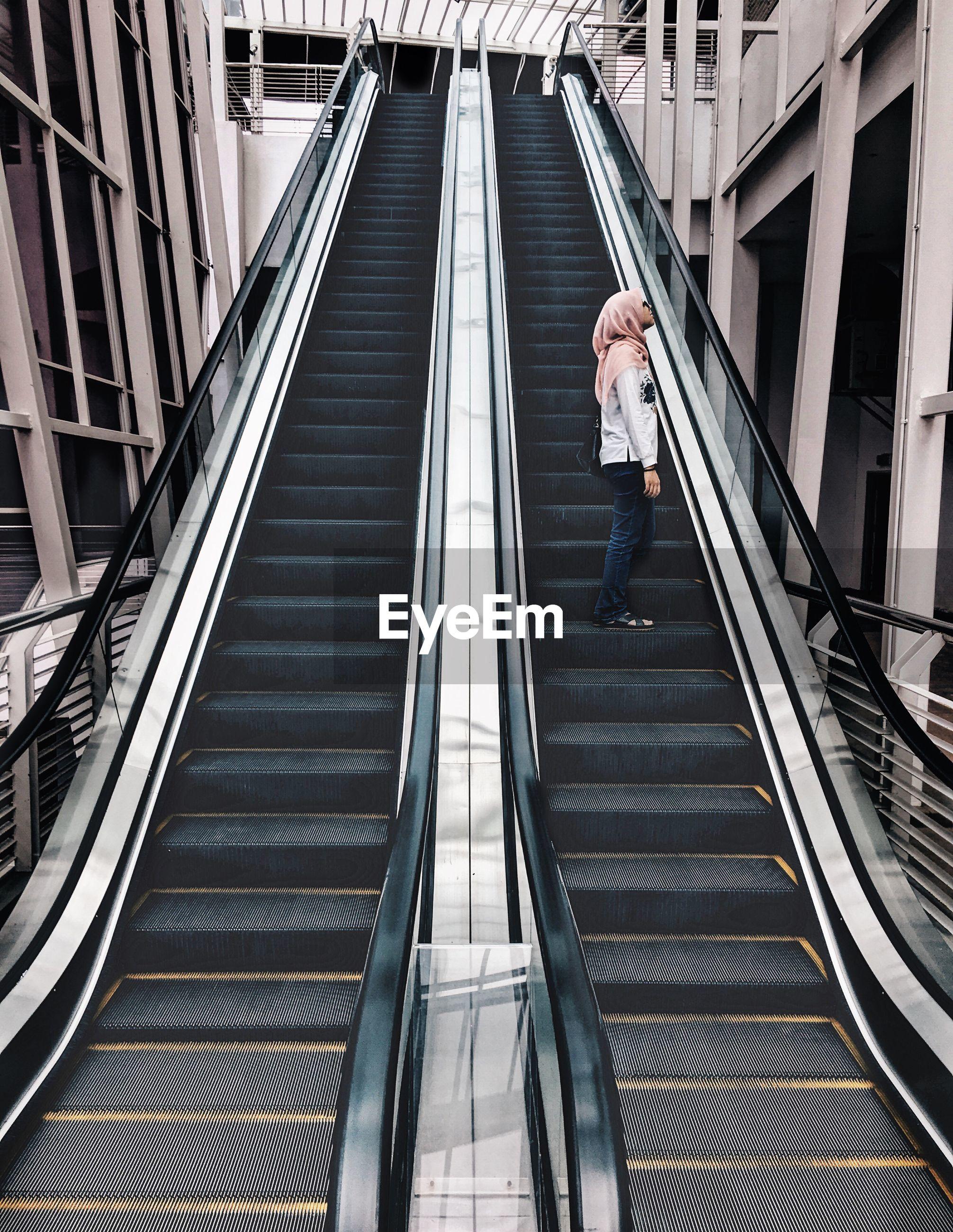 Woman standing on escalator
