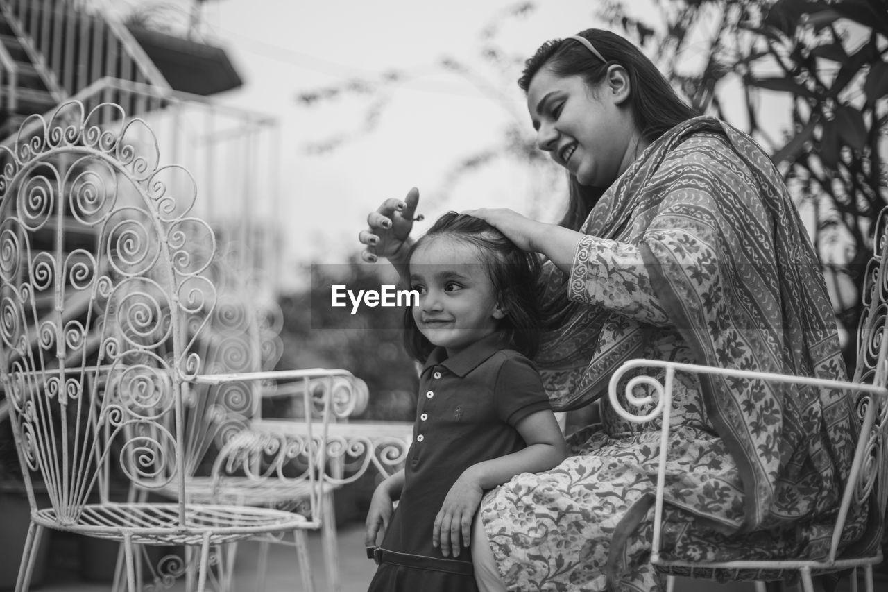 Smiling Mother Tying Daughter Hair