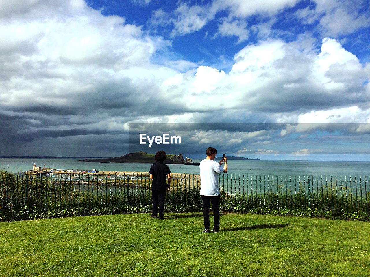 sky, cloud - sky, grass, real people, beauty in nature, land, men, plant, standing, nature, two people, full length, lifestyles, water, leisure activity, day, rear view, sea, scenics - nature, horizon over water, outdoors, couple - relationship, positive emotion