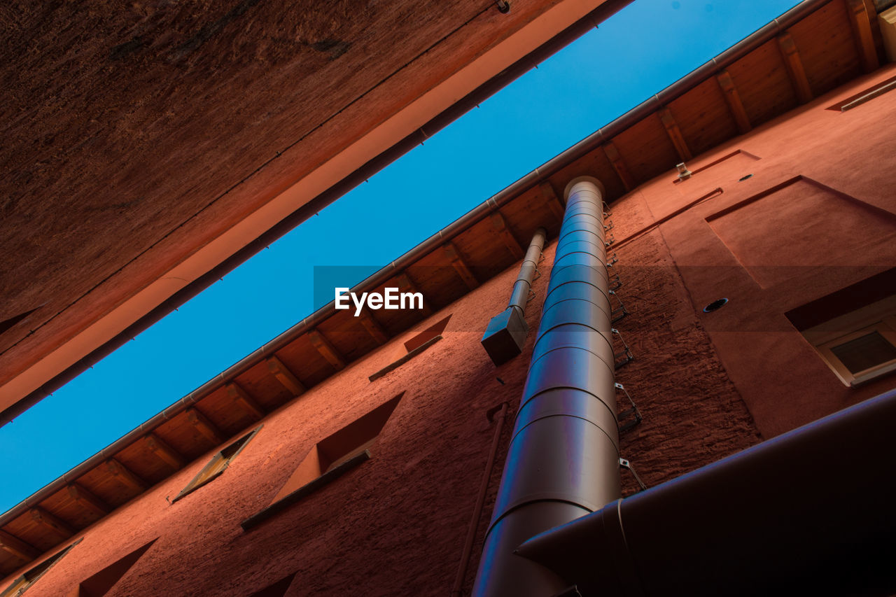 Low Angle View Of Water Pipe On Building Against Sky
