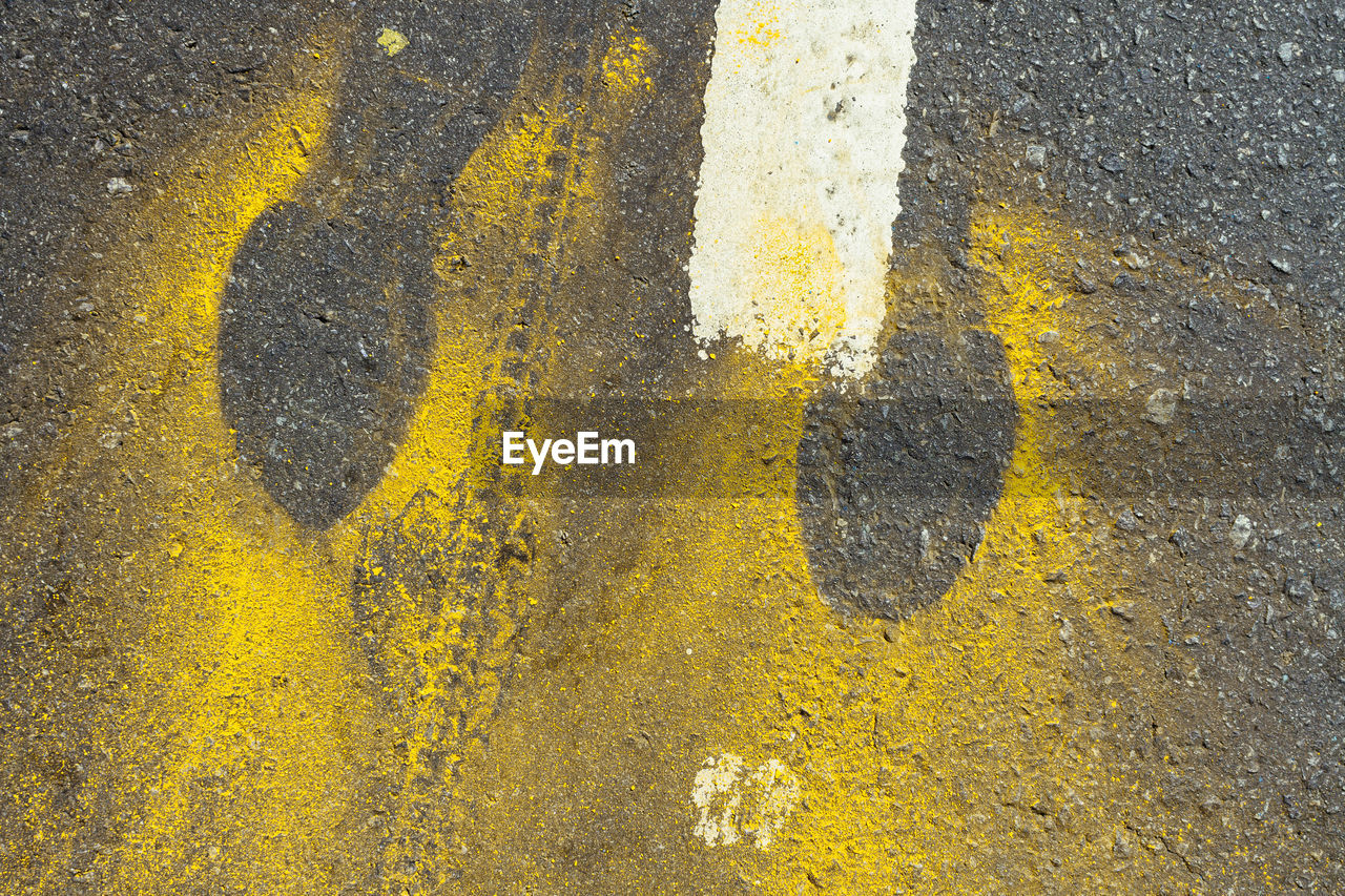 Close-Up Of Powered Paint Amidst Footprint On Road