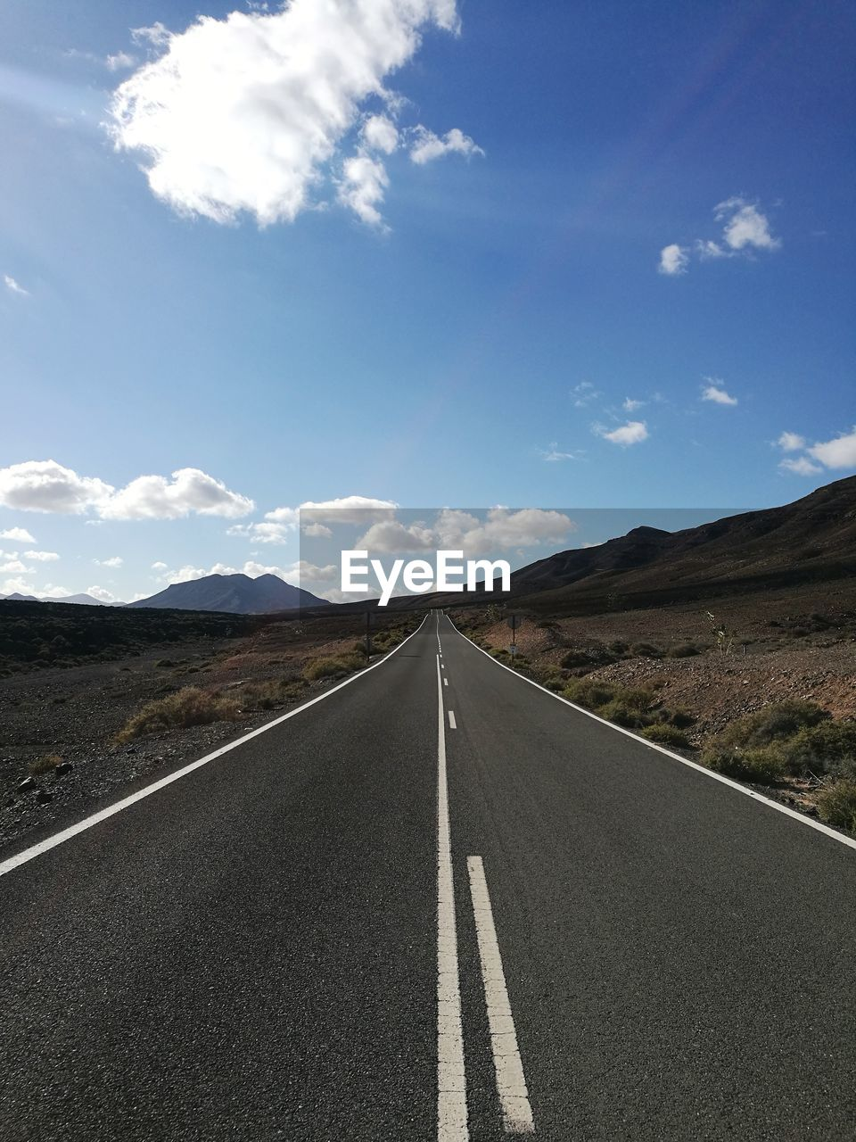 road, sky, direction, transportation, cloud - sky, symbol, road marking, marking, sign, the way forward, diminishing perspective, landscape, environment, mountain, nature, non-urban scene, scenics - nature, vanishing point, tranquility, beauty in nature, no people, mountain range, outdoors, dividing line