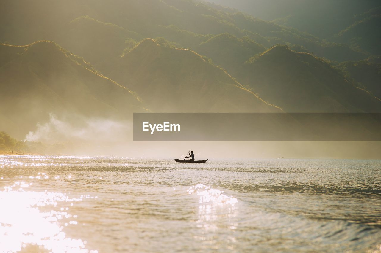Silhouette Man Rowing Boat On River Against Mountains