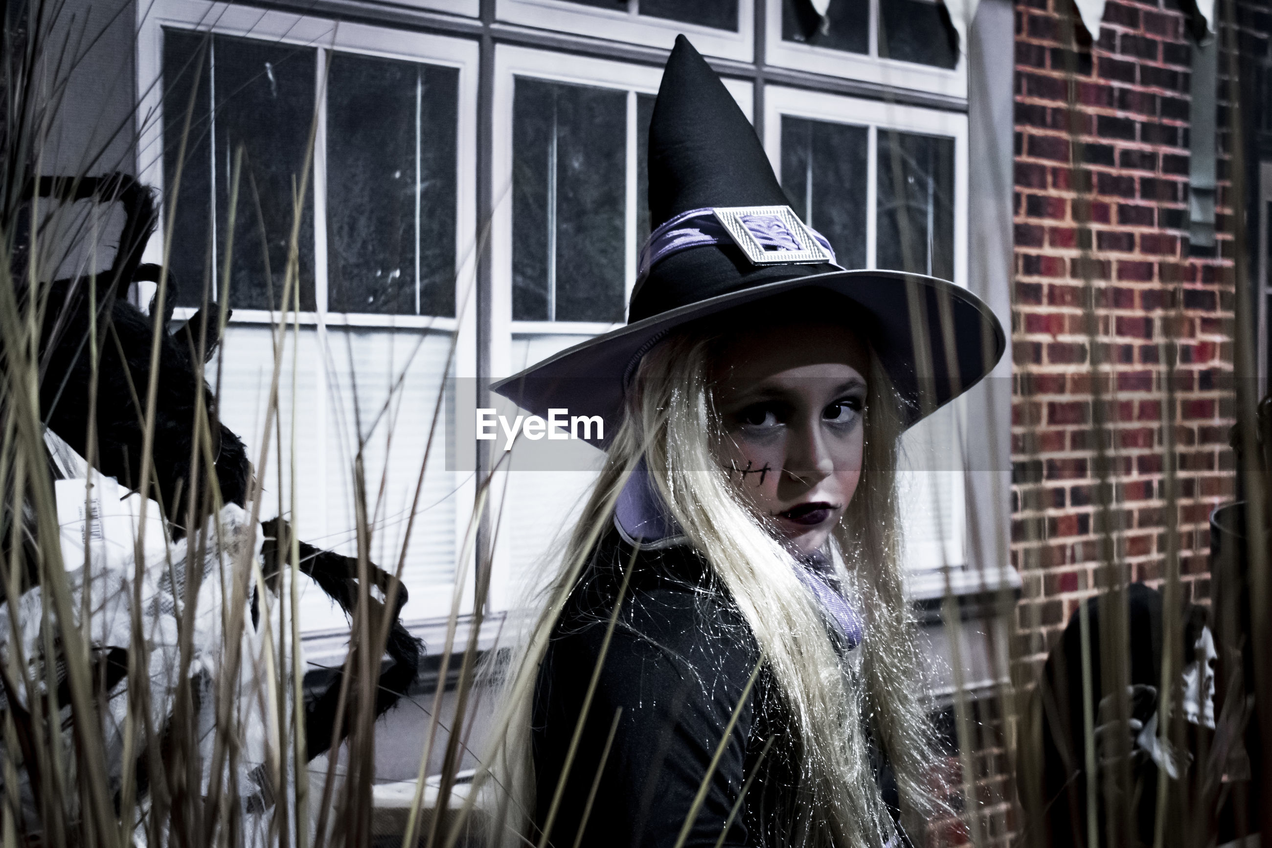 Portrait of girl wearing witch costume against house during halloween