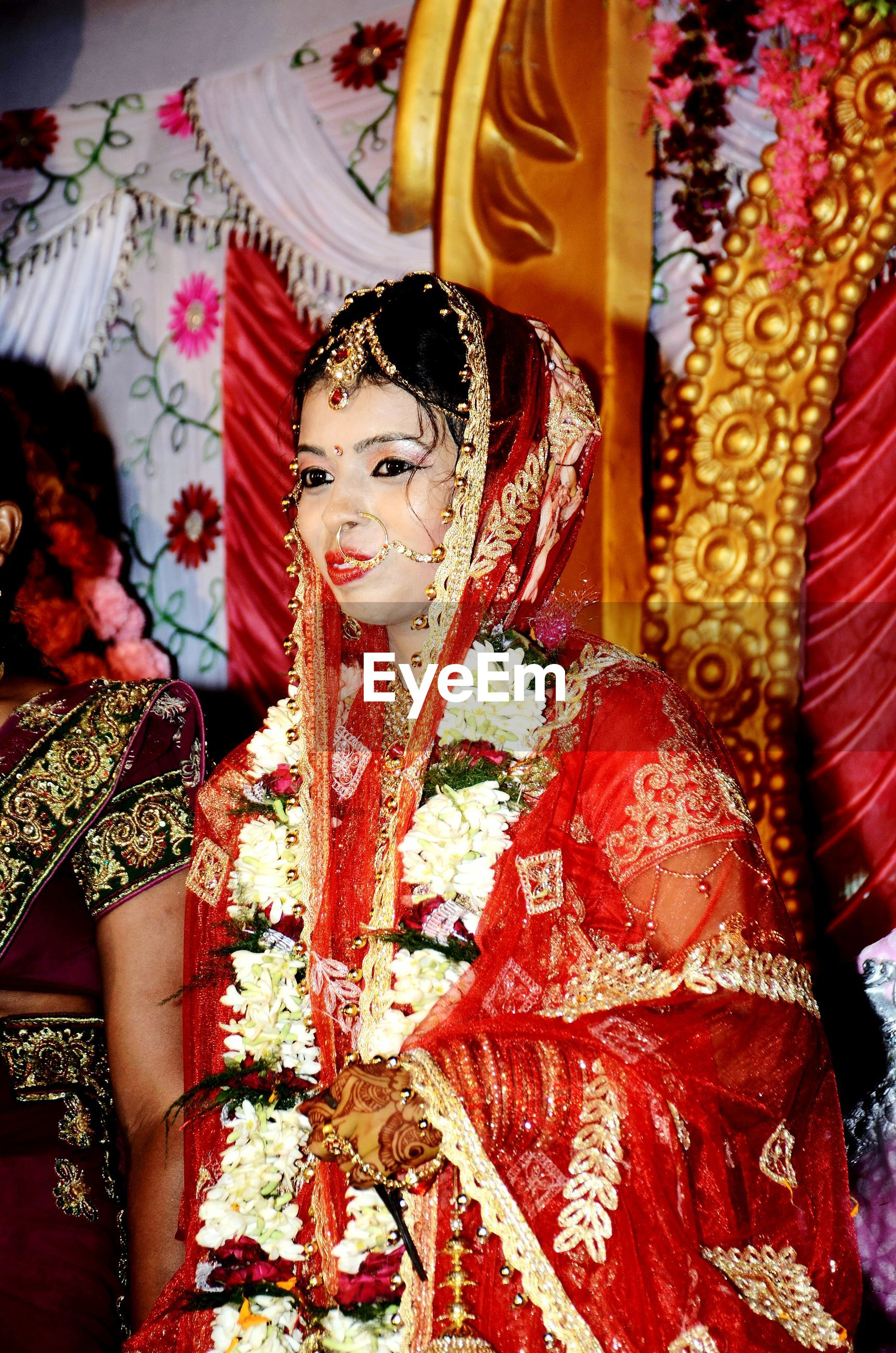 Bride in red sari standing against decoration during wedding ceremony