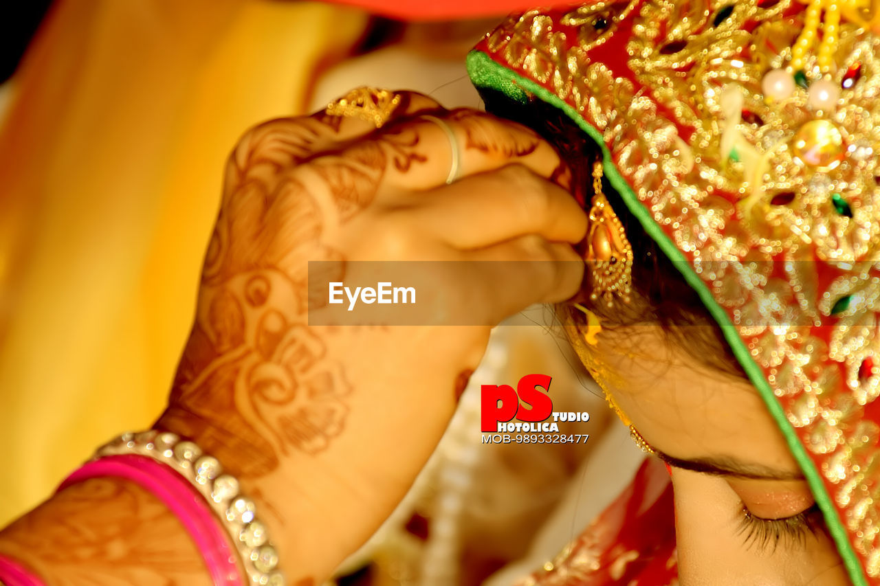 bride, henna tattoo, life events, traditional clothing, celebration, wedding, real people, human hand, women, holding, cultures, gold colored, indoors, midsection, wedding ceremony, tradition, human body part, close-up, lifestyles, ceremony, wedding dress, groom, day, adult, people