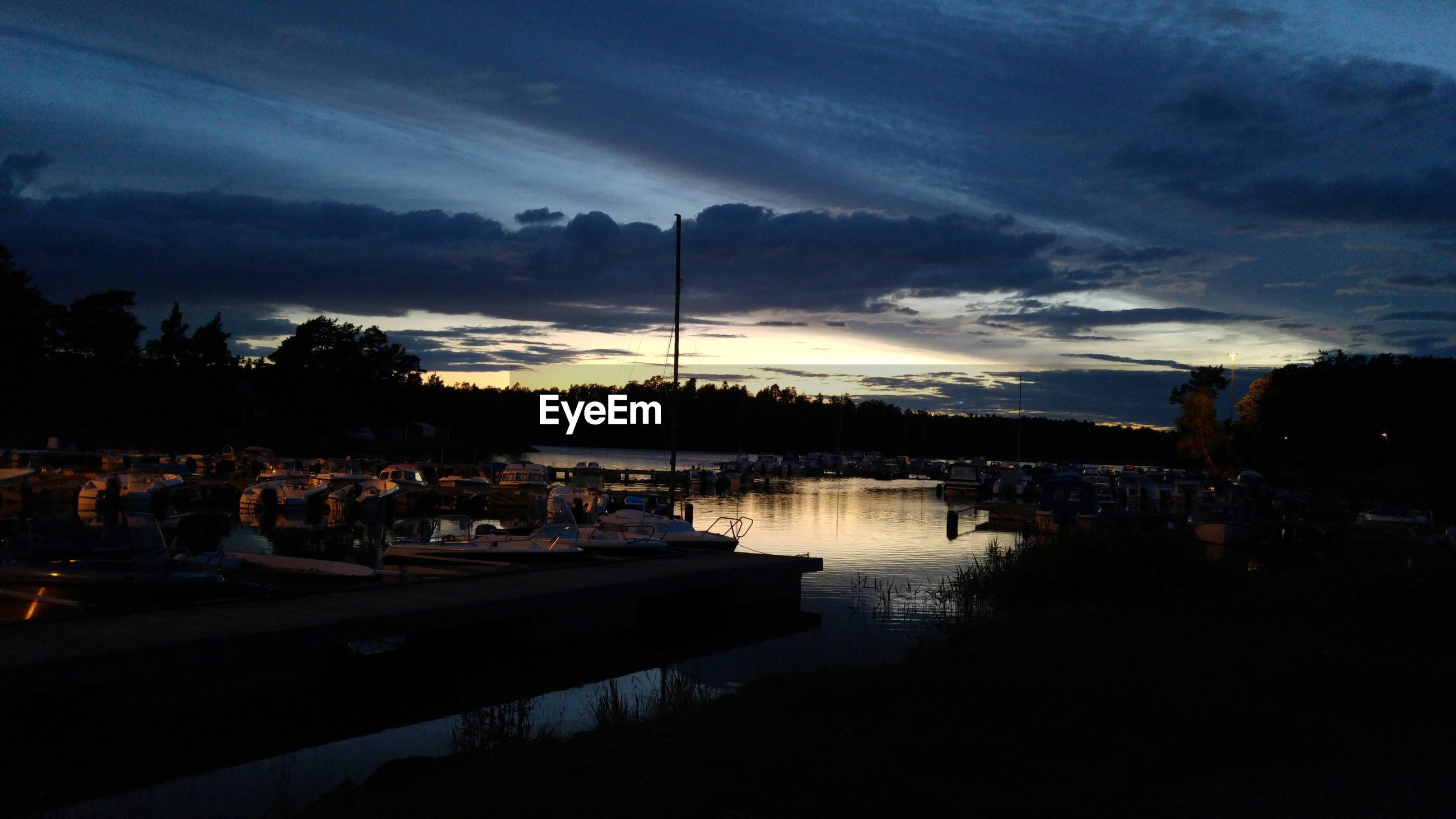 Boats moored at harbor against sky during dusk