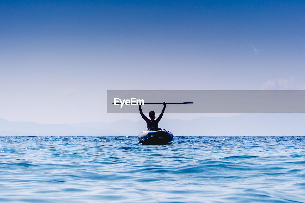Woman Holding Oar Moving In Boat On Sea Against Sky