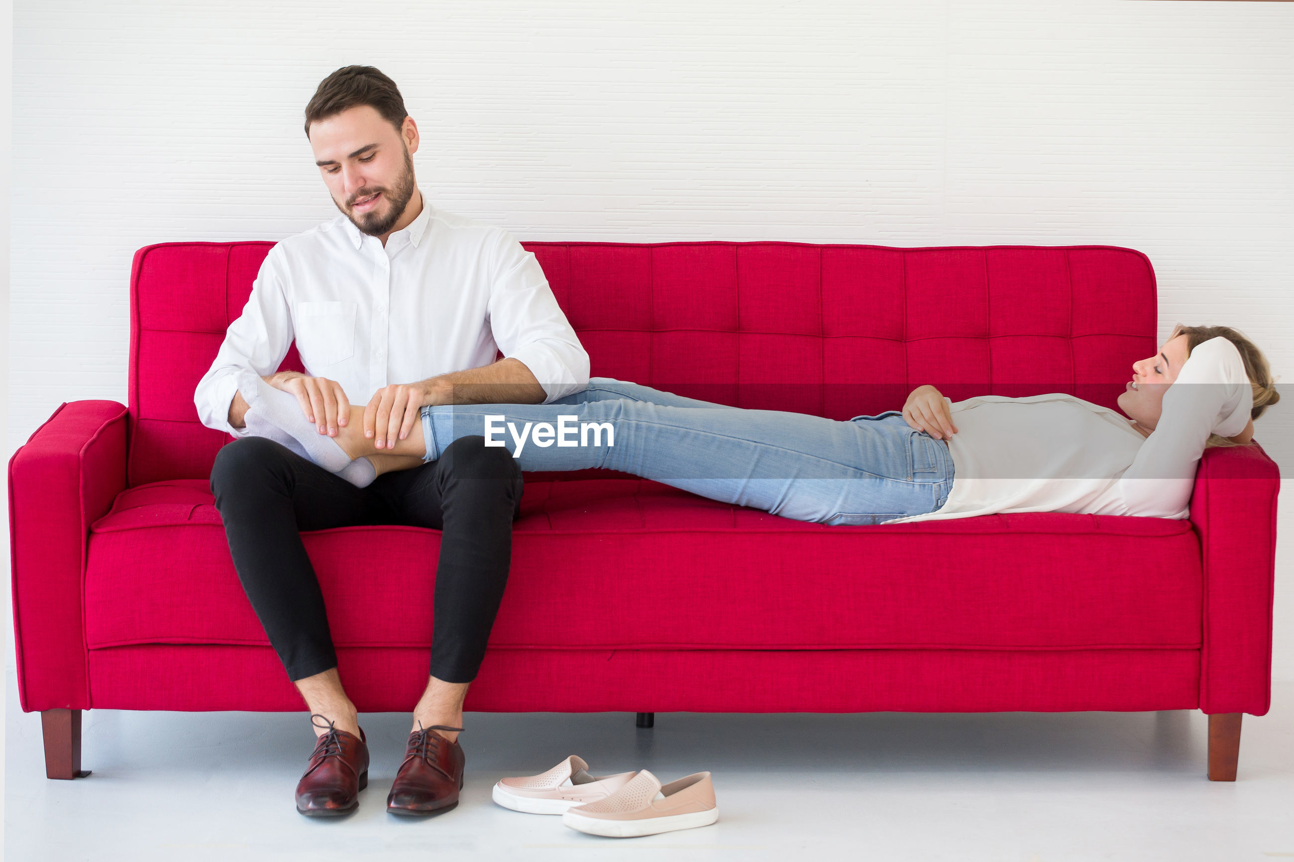 Boyfriend massaging girlfriend foot on sofa against white wall