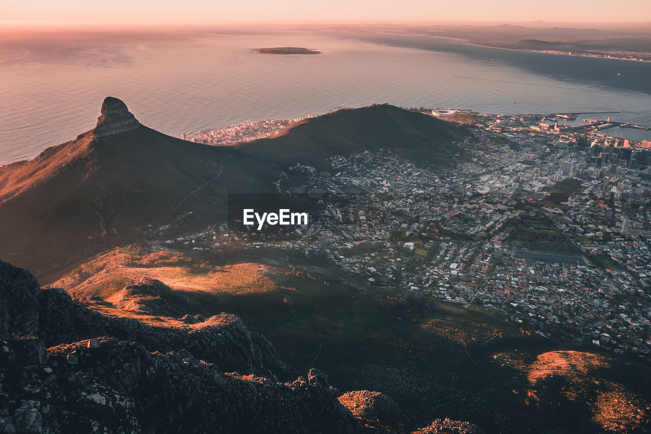 Aerial view of cityscape by sea at sunset