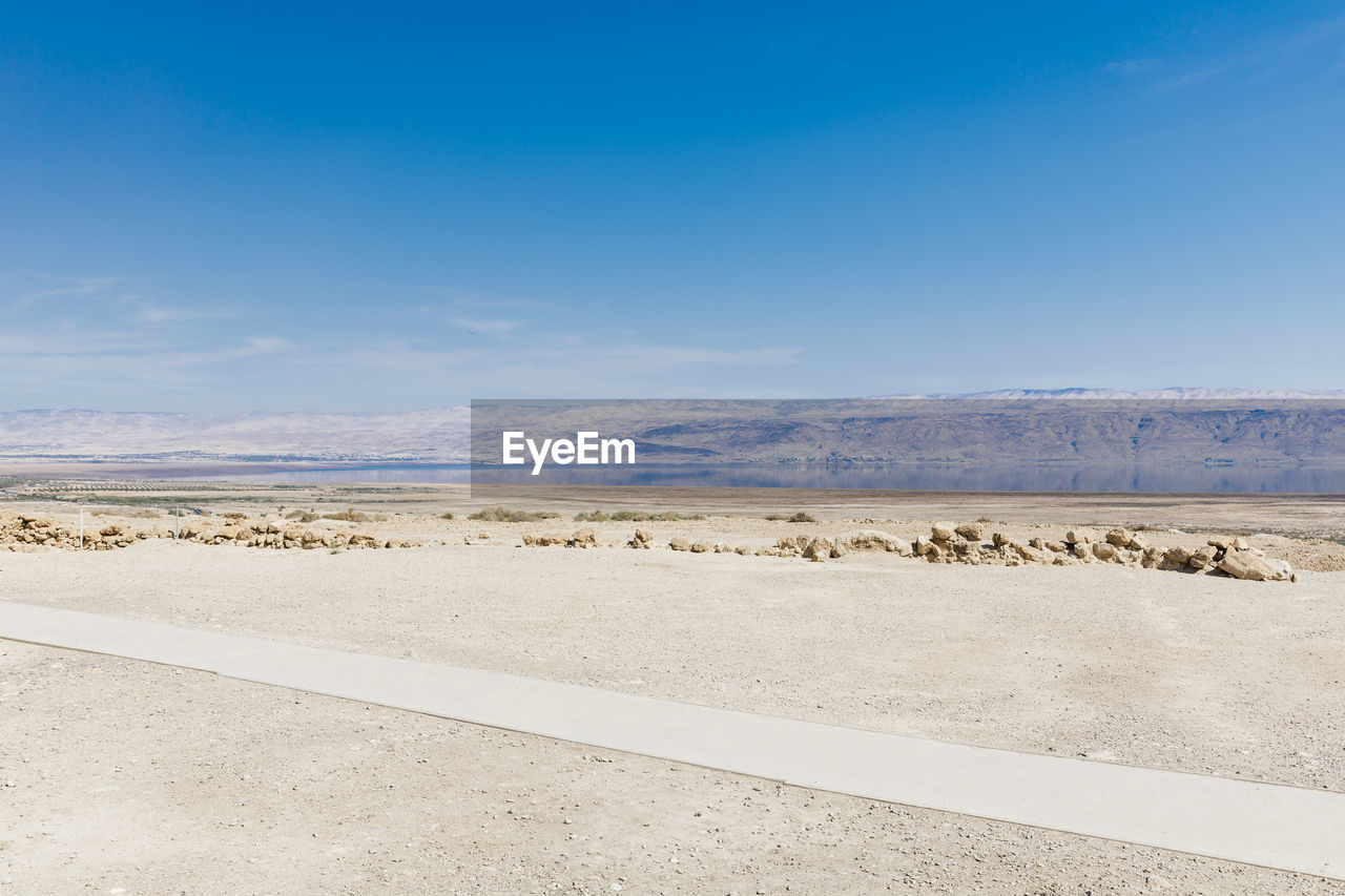 sky, road, environment, scenics - nature, beauty in nature, landscape, tranquil scene, tranquility, non-urban scene, blue, nature, no people, transportation, day, desert, land, cloud - sky, remote, outdoors, arid climate, climate, salt flat
